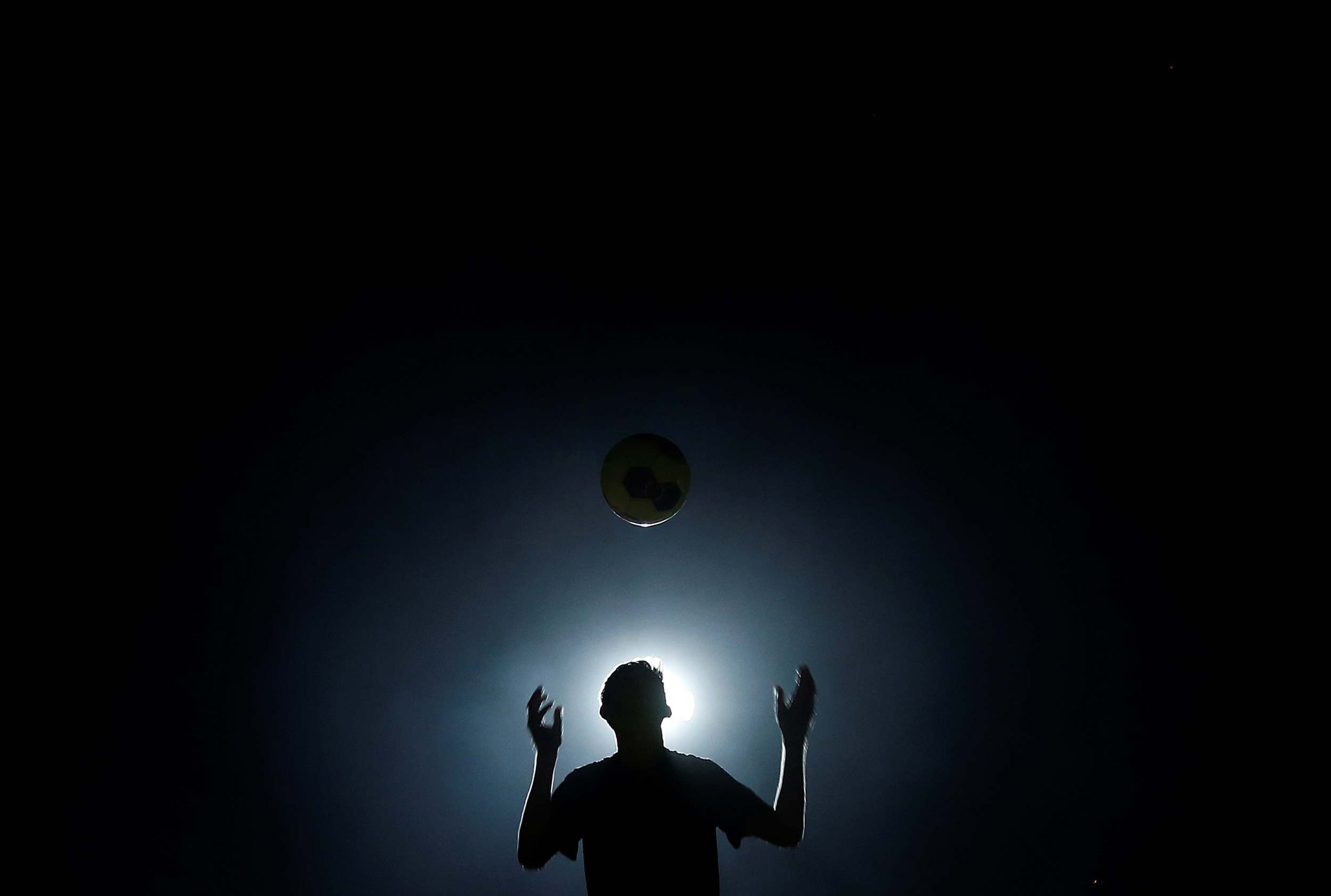 Boy is silhouetted as he plays with a soccer ball at night in Colombo...A boy is silhouetted as he plays with a soccer ball at night in Colombo June 11, 2014. The 2014 FIFA soccer World Cup will be held in Brazil from June 12 through July 13. REUTERS/Dinuka Liyanawatte (SRI LANKA - Tags: SPORT SOCCER WORLD CUP TPX IMAGES OF THE DAY)
