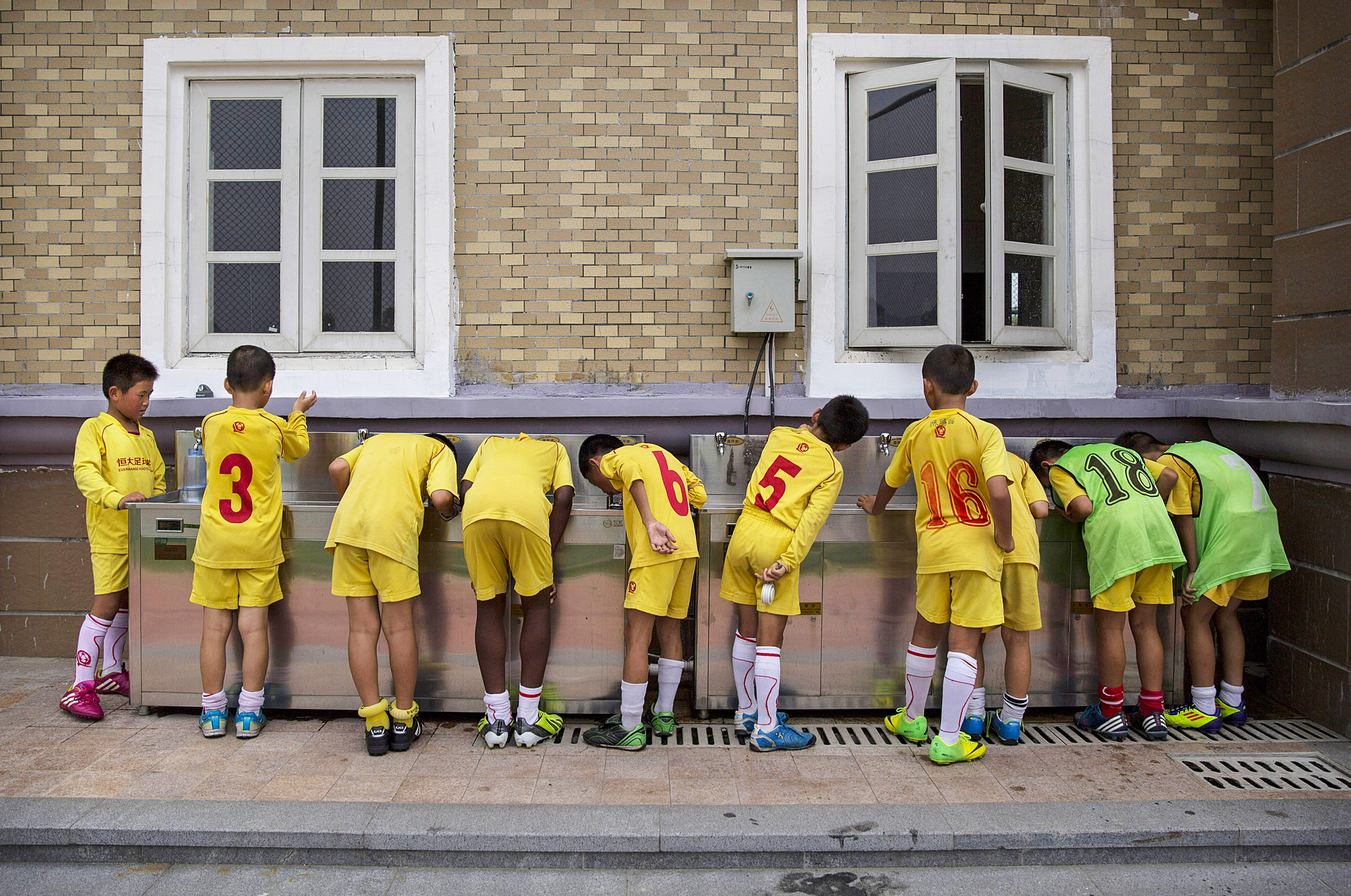 China Sets Sights on Future Glory With World's Biggest Football Academy...QINGYUAN, CHINA - JUNE 12:  Young Chinese football players drink water from a communal tap after training at the Evergrande International Football School on June 12, 2014 near Qingyuan in Guangdong Province, China. The sprawling 167-acre campus is the brainchild of property tycoon Xu Jiayin, whose ambition is to train a generation of young athletes to establish China as a football powerhouse. The school is considered the largest football academy in the world with 2400 students, more than 50 pitches and a squad of Spanish coaches through a partnership with Real Madrid. (Photo by Kevin Frayer/Getty Images)