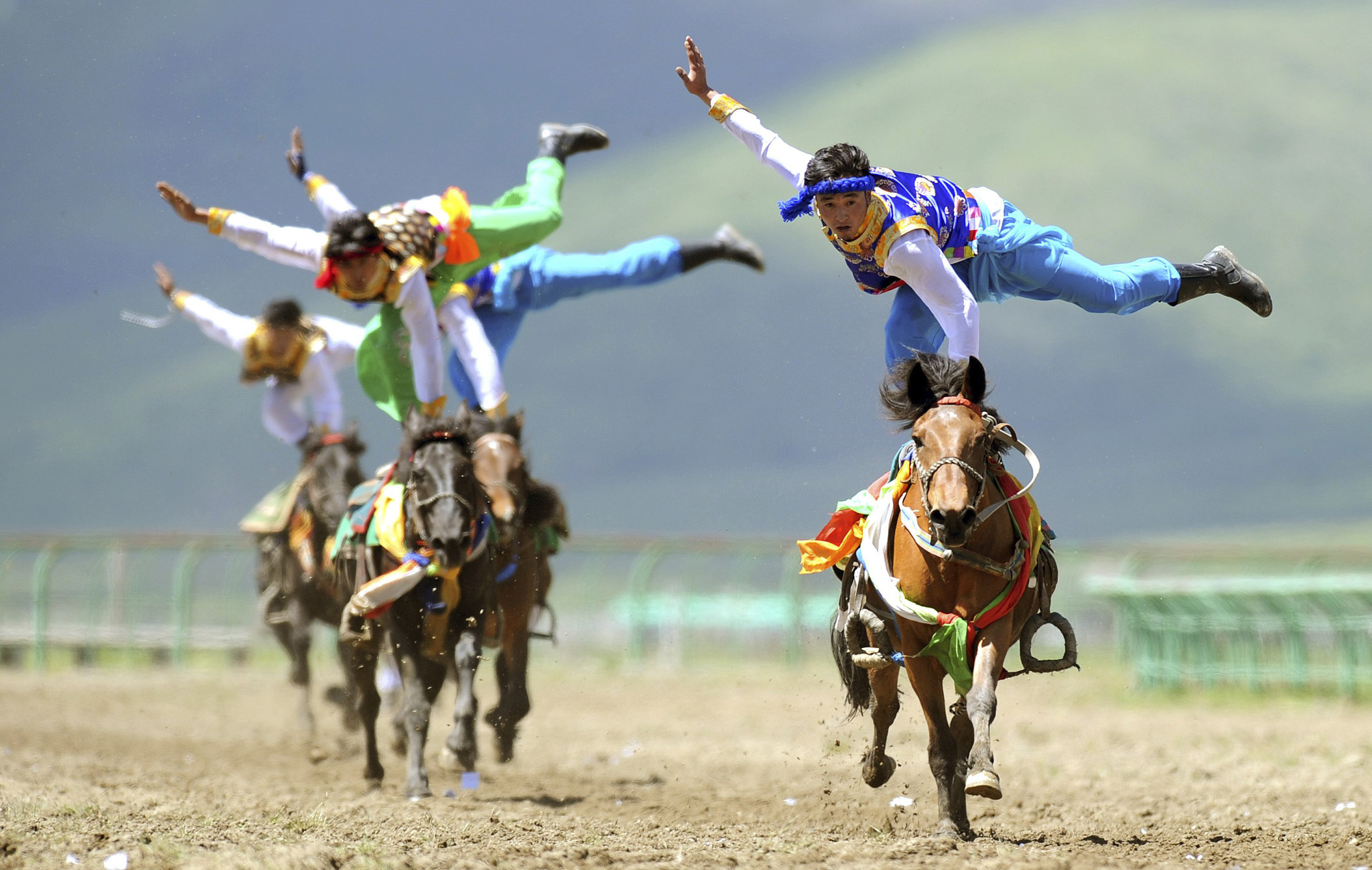 Tibetan participants perform on horses during a traditional equestrian competition in Aba Tibetan and Qiang Autonomous Prefecture...Tibetan participants perform on horses during a traditional equestrian competition in Hongyuan county of Aba Tibetan and Qiang Autonomous Prefecture, Sichuan Province June 17, 2014. Picture taken June 17, 2014. REUTERS/China Daily (CHINA - Tags: SOCIETY ANIMALS TPX IMAGES OF THE DAY) CHINA OUT. NO COMMERCIAL OR EDITORIAL SALES IN CHINA