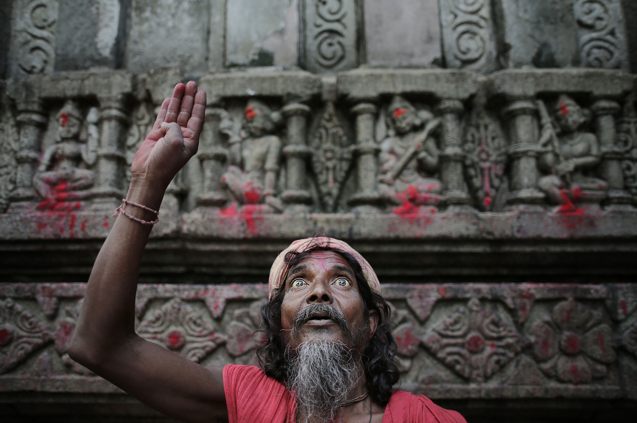 A man gestures to attract alms from devotees at the Kamakhya Hindu temple during the Ambubasi festival in Gauhati, India, Wednesday, June 25, 2014. The annual festival where hundreds of holy men from an esoteric form of Hinduism, gather to perform rituals ends Thursday. (AP Photo/Anupam Nath)