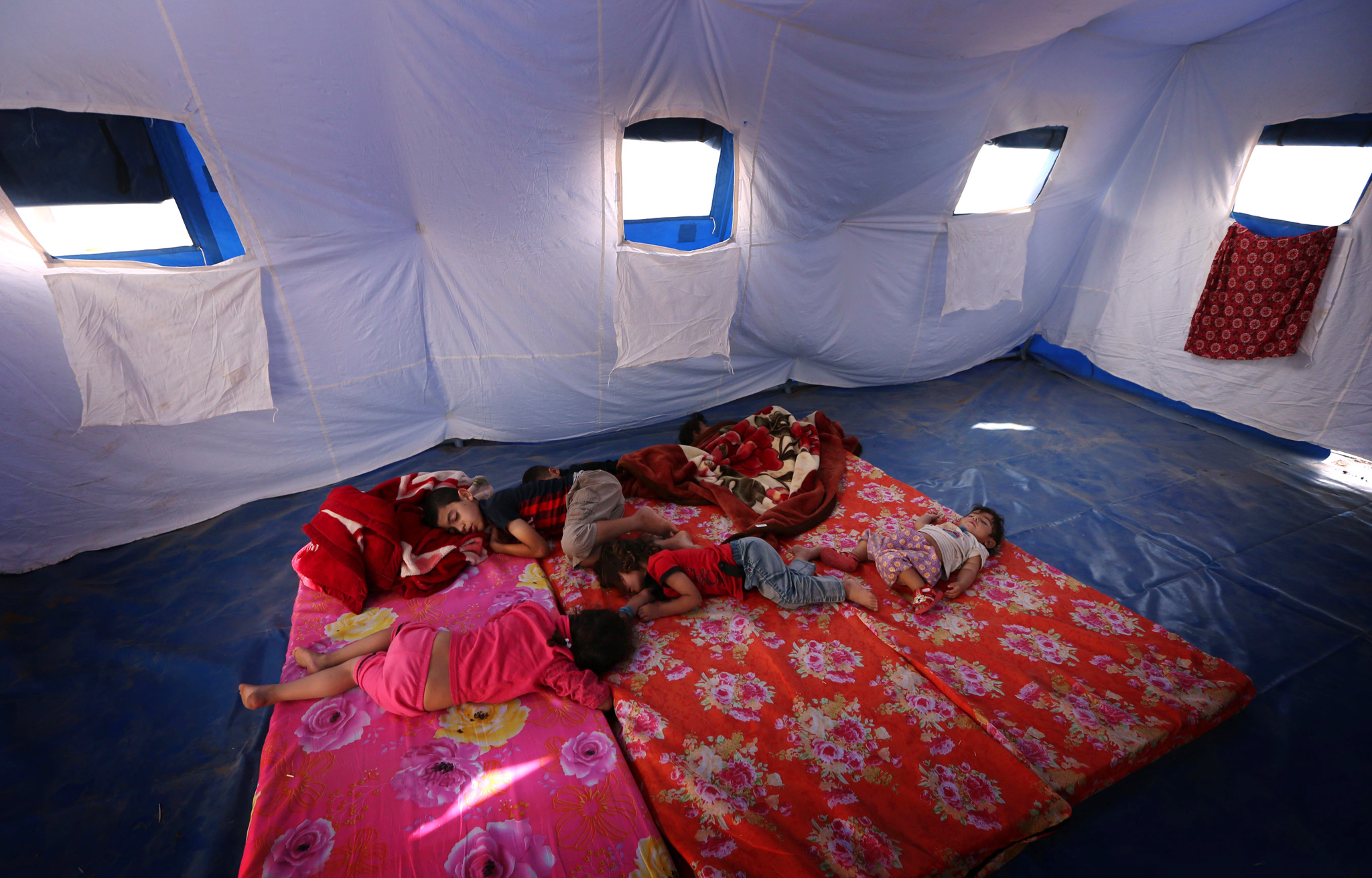 TOPSHOTS Iraqi children fleeing violence...TOPSHOTS Iraqi children fleeing violence in the northern Nineveh province sleep in a tent at a temporary camp in Aski kalak, 40 kms West of Arbil, in the autonomous Kurdistan region, on June 12, 2014. Thousands of people who fled Iraq's second city of Mosul after it was overrun by jihadists wait in the blistering heat, hoping to enter the safety of the nearby Kurdish region and furious at Baghdad's failure to help them.  many as half a million people are thought to have fled Mosul, which was captured by the Islamic State of Iraq and the Levant (ISIL) Tuesday after a spectacular assault that routed the army. AFP PHOTO/SAFIN HAMEDSAFIN HAMED/AFP/Getty Images
