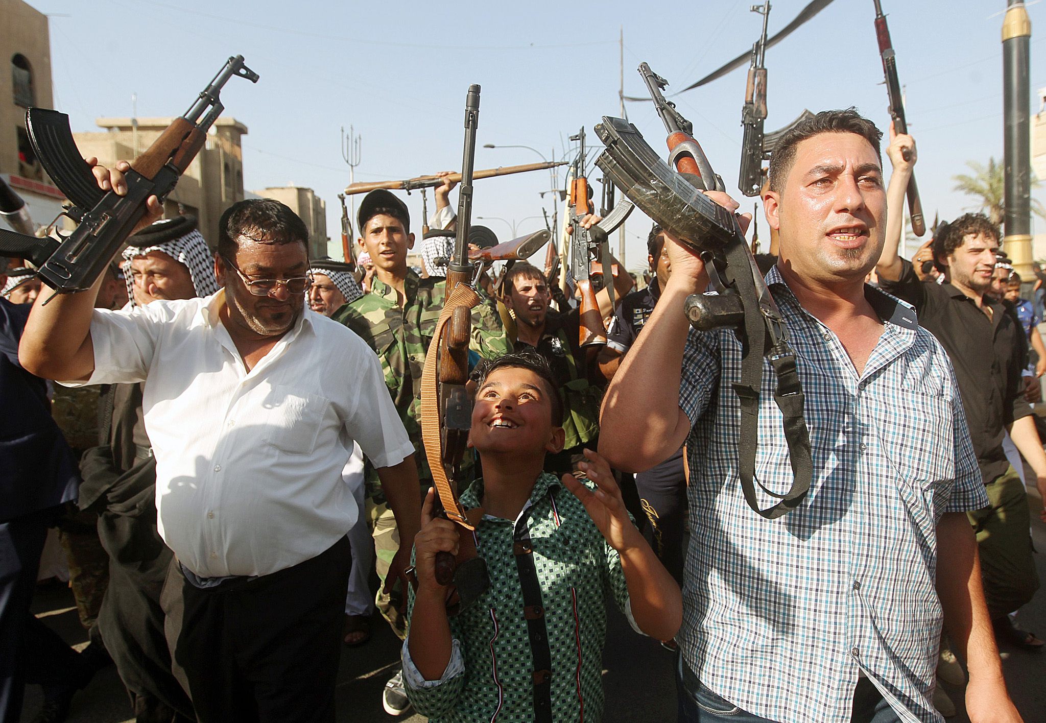 TOPSHOTS A Iraqi young boy and tribesmen...TOPSHOTS A Iraqi young boy and tribesmen hold up their weapons as they gather to show their readiness to join Iraqi security forces in the fight against Jihadist militants who have taken over several northern Iraqi cities on June 16, 2014 in the capital Baghdad. Faced with a militant offensive sweeping south toward Baghdad, Prime Minister Nuri al-Maliki announced the Iraqi government would arm and equip civilians who volunteer to fight, and thousands have signed up.   AFP PHOTO/AHMAD AL-RUBAYEAHMAD AL-RUBAYE/AFP/Getty Images