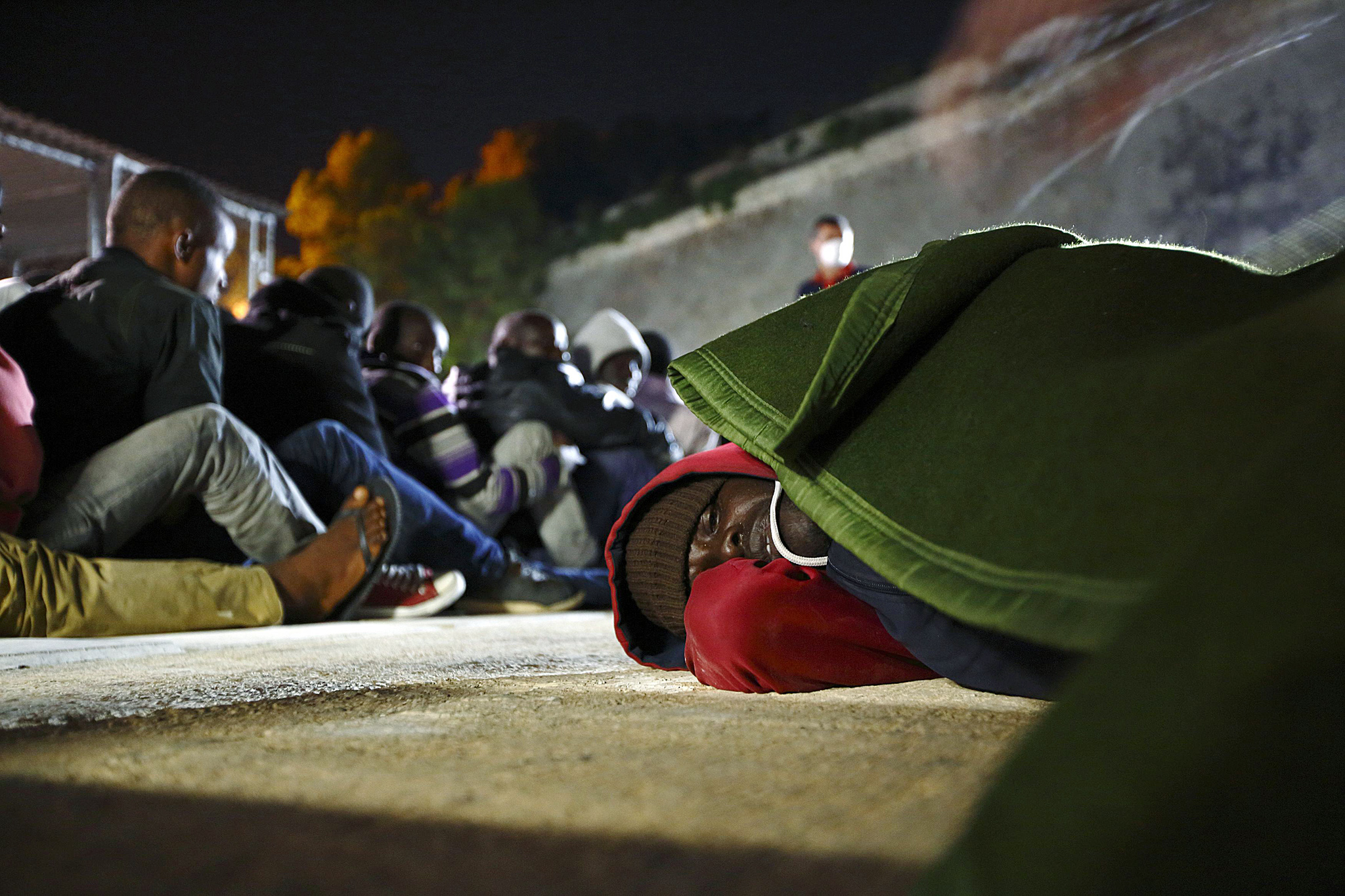 Ill irregular immigrant lies on the ground as a blanket is placed over him at Armed Forces of Malta Maritime Squadron base at Haywharf in Valletta's Marsamxett Harbour...An ill irregular immigrant lies on the ground as a blanket is placed over him at the Armed Forces of Malta (AFM) Maritime Squadron base at Haywharf in Valletta's Marsamxett Harbour, early June 8, 2014. A group of 130 Sub-Saharan African migrants were rescued by the AFM south of the Maltese islands when their boat ran into difficulties, according to army sources.  REUTERS/Darrin Zammit Lupi (MALTA - Tags: SOCIETY IMMIGRATION TPX IMAGES OF THE DAY)