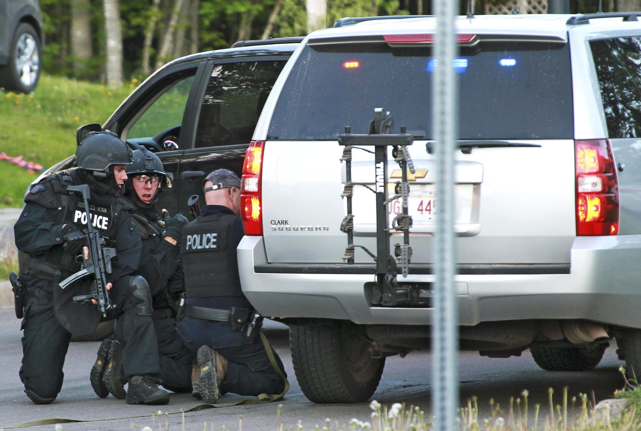Emergency Response team members take cover behind vehicles in Moncton