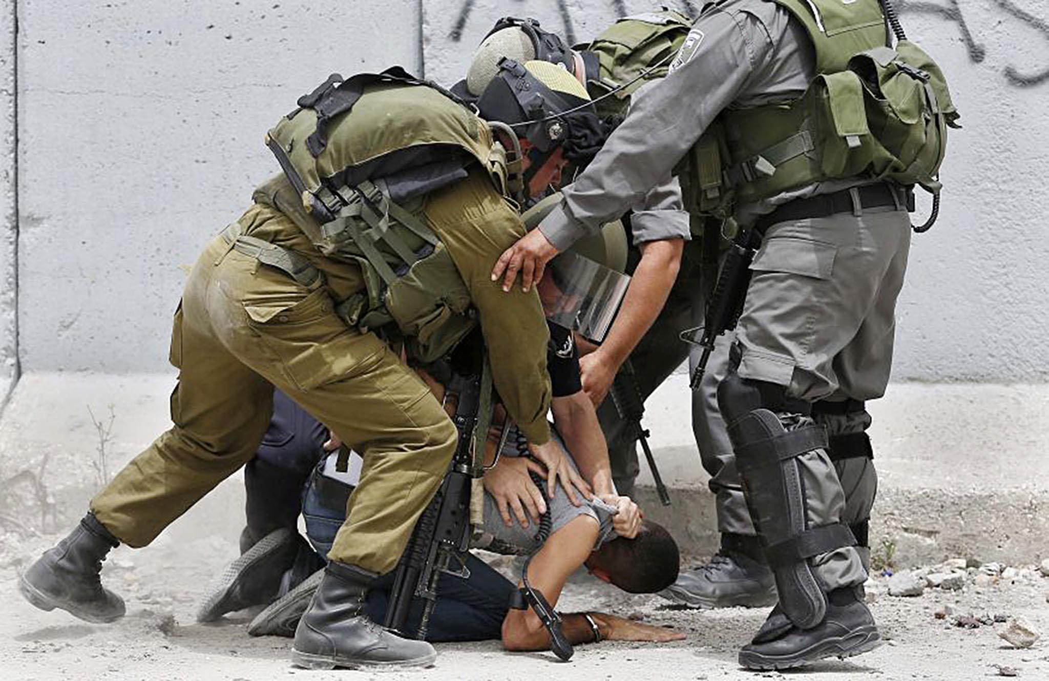 "sraeli soldiers and border police detain a Palestinian during a protest in solidarity with prisoners on hunger strike, at Qalandia checkpoint near the West Bank city of Ramallah...Israeli soldiers and border police detain a Palestinian during a protest in solidarity with prisoners on hunger strike, at Qalandia checkpoint near the West Bank city of Ramallah June 5, 2014. Some 120 Palestinians jailed without trial in Israel have been on an open-ended hunger strike, eating only salt and drinking water, since April 24 to demand an end to so-called ""administrative detention"". REUTERS/Mohamad Torokman (WEST"