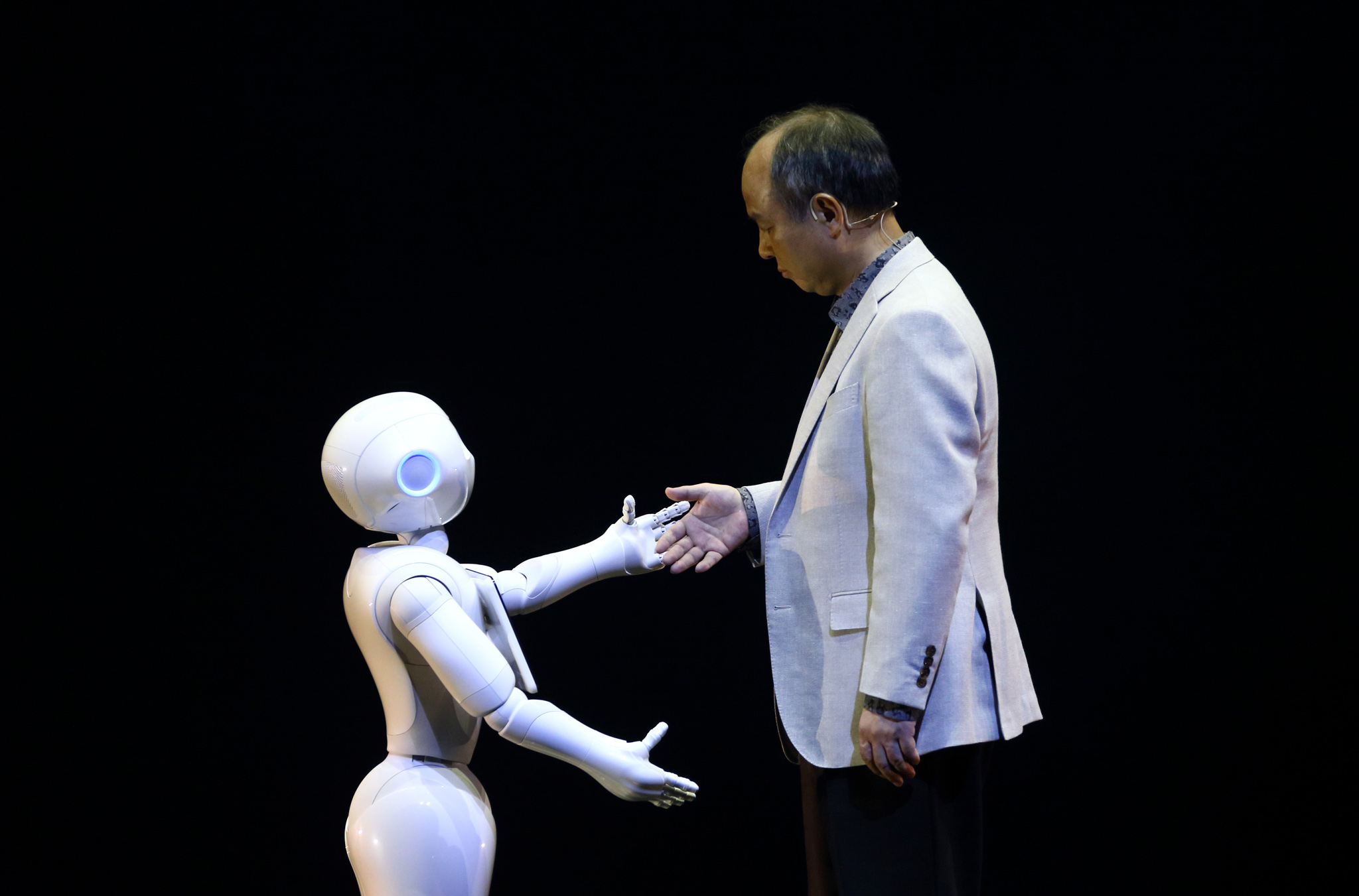 Softbank Chief Executive Officer Masayoshi Son News Conference...Billionaire Masayoshi Son, chairman and chief executive officer of SoftBank Corp., right, offers his hand to a human-like robot called Pepper, developed by the company's Aldebaran Robotics unit, during a news conference in Urayasu, Chiba Prefecture, Japan, on Thursday, June 5, 2014. SoftBank plans to sell interactive robots for households from February next year. Photographer: Tomohiro Ohsumi/Bloomberg *** Local Caption *** Masayoshi Son