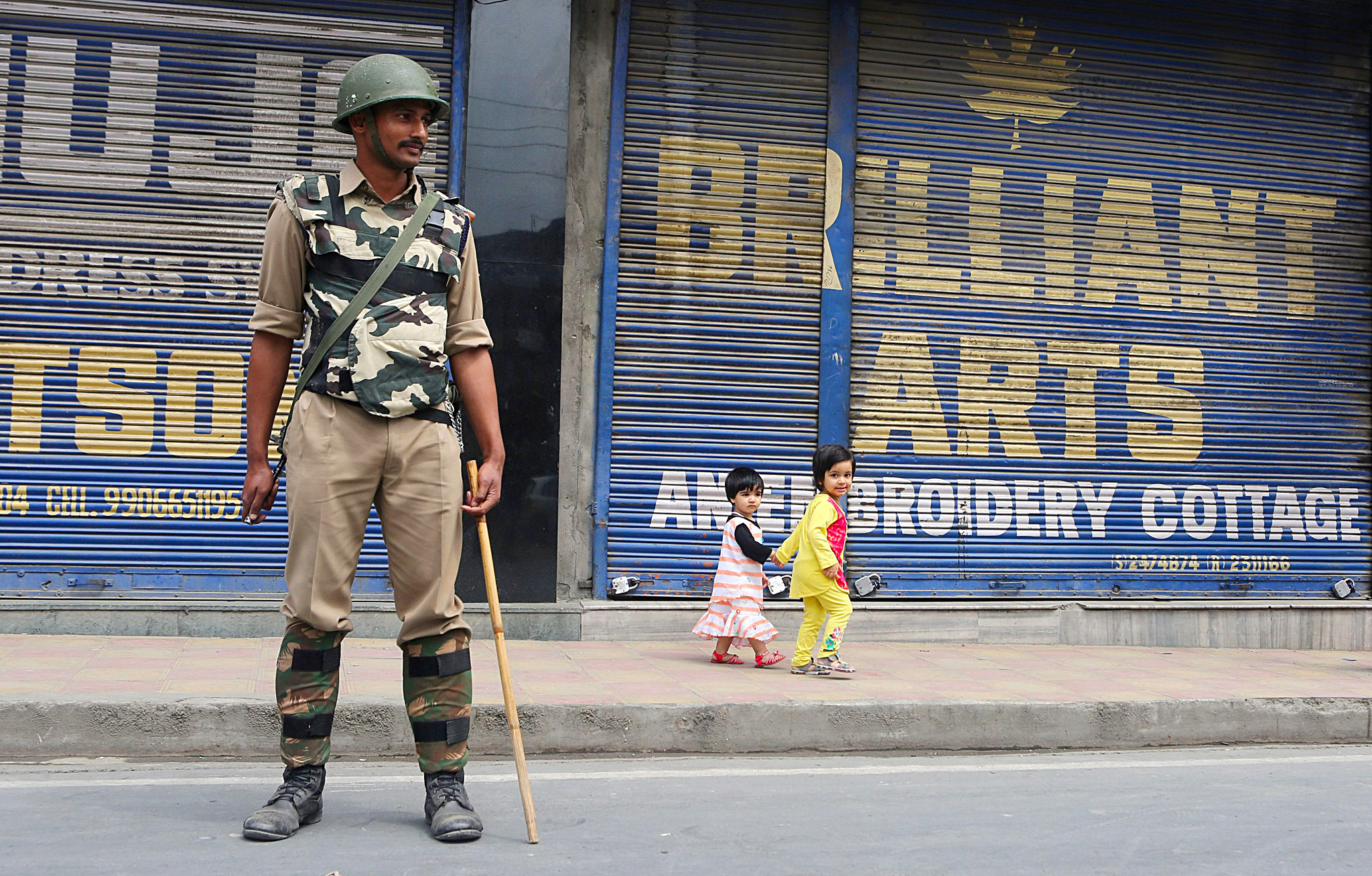 Shutdown in Srinagar...epa04273978 Kashmiri children walk past as an Indian paramilitary soldier standing guard in front of closed shops during a shutdown in Srinagar, the summer capital of Indian Kashmir, 23 June 2014. Indian police detained Muhammad Yasin Malik, Chairman of Jammu and Kashmir Liberation Front (JKLF), along with his supporters in Srinagar. Malik was evading arrest ahead of his Monday's 'Quit Kashmir' programme. Indian Kashmir is observing a complete shutdown in response to the JKLF call against New Delhi's rule. Authorities have deployed contingents of police and paramilitary at several places to foil JKLF's protest programme.  EPA/FAROOQ KHAN