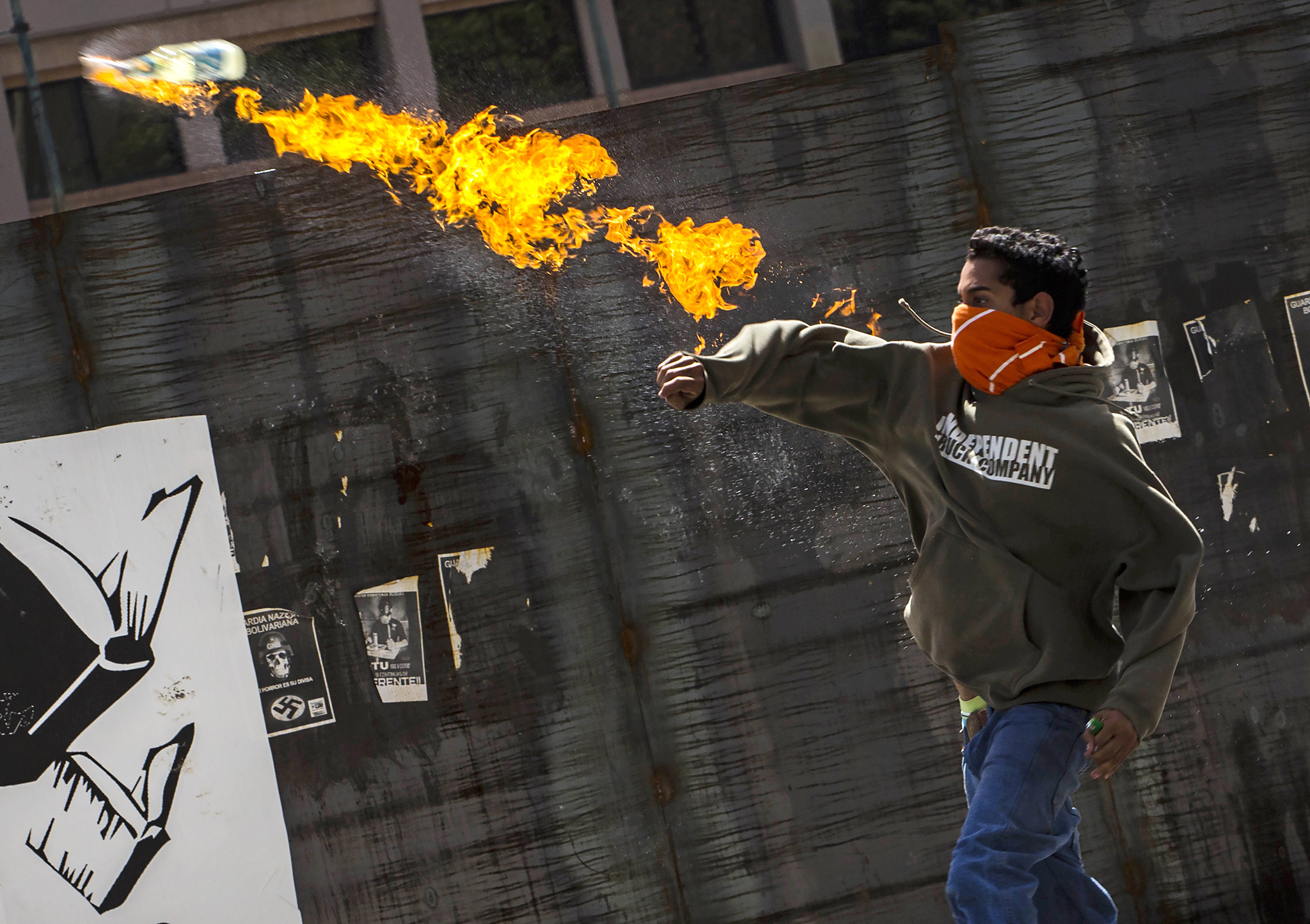 A protester throws a molotov cocktail at Bolivarian National Police during a protest against the government of President Nicolas Maduro in Caracas, Venezuela, Tuesday, June 24, 2014. University students and government opponents protested in the east of the capital and demanded the release of people who have been arrested in street demonstrations in recent months. (AP Photo/Ramon Espinosa)