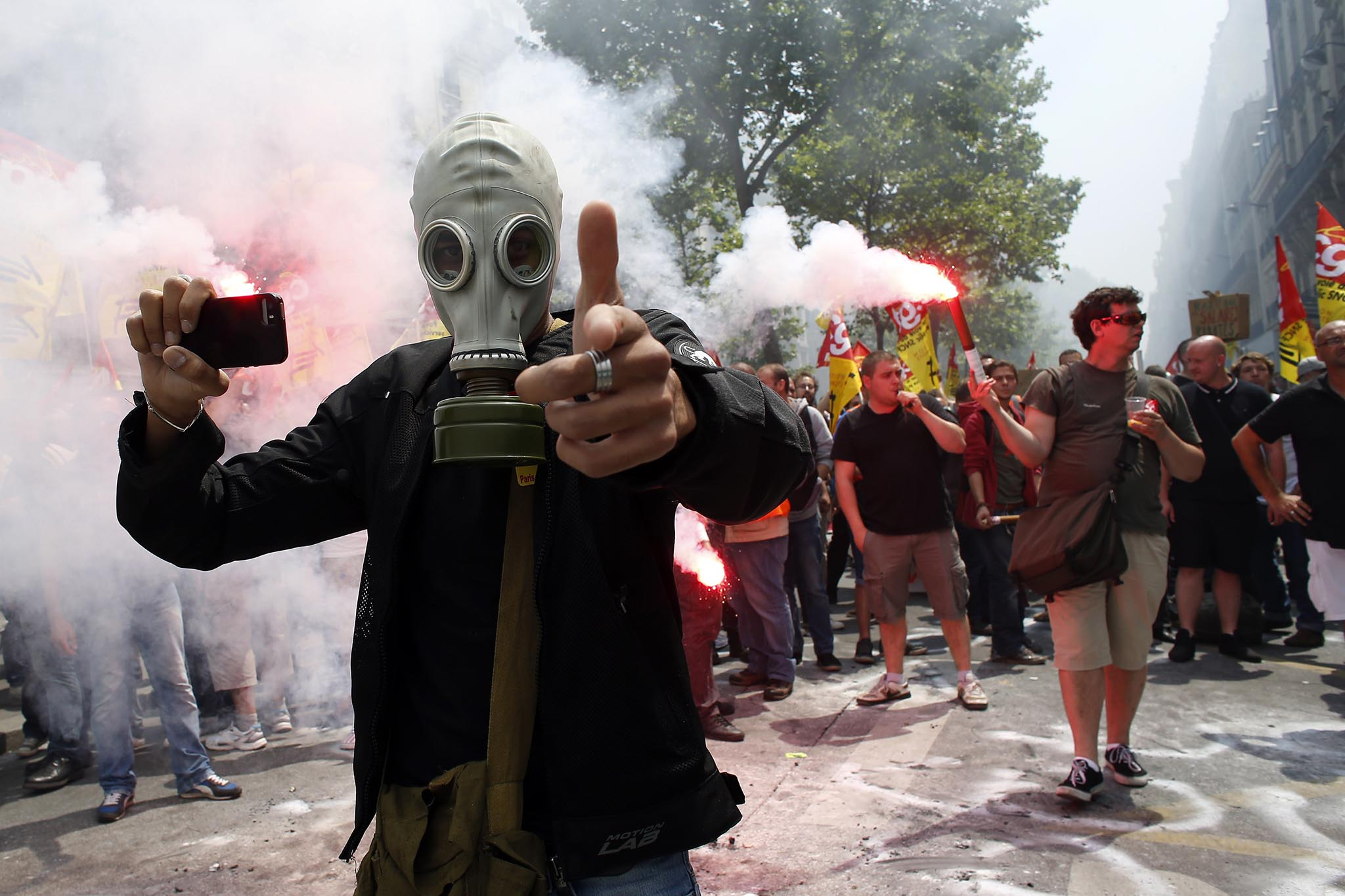 A protester wearing a gas mask holds a smartphone and gestures