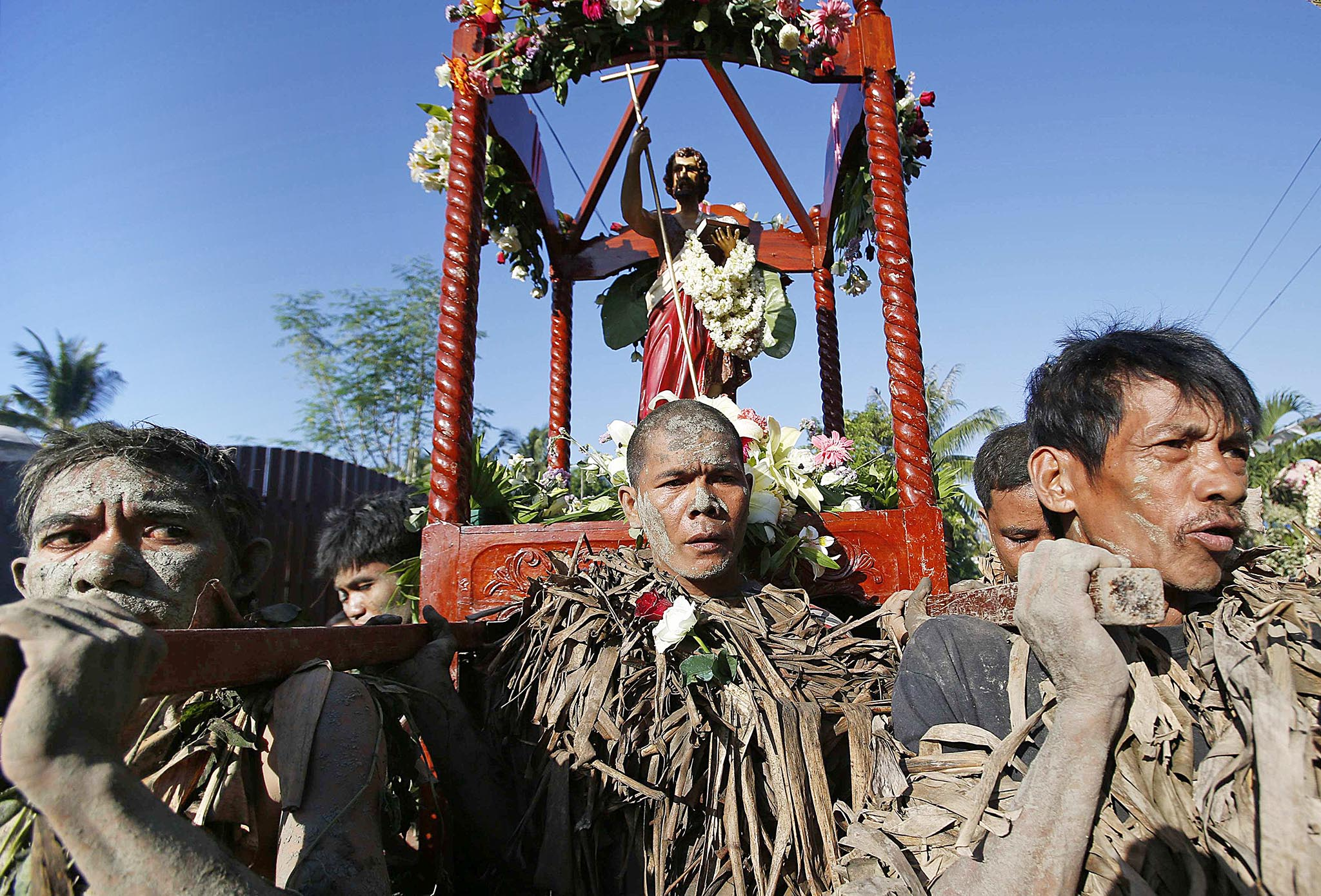 "Devotees carry a statue of Saint John the Baptist as they take part in a religious ritual known locally as ""Taong Putik"", while celebrating the feast day of their Catholic patron saint in the village of Bibiclat"