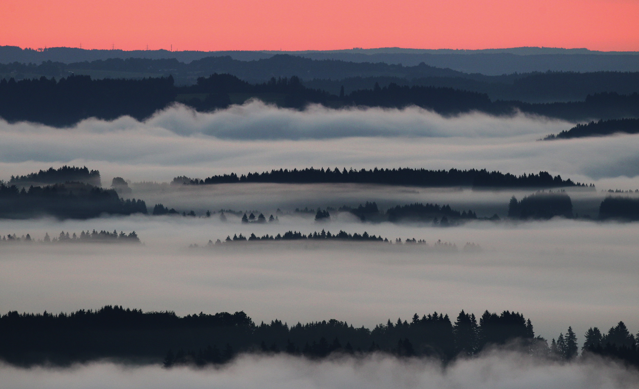 Morning fog covers the valleys near Bernbeuren, southern Germany, at sunrise.