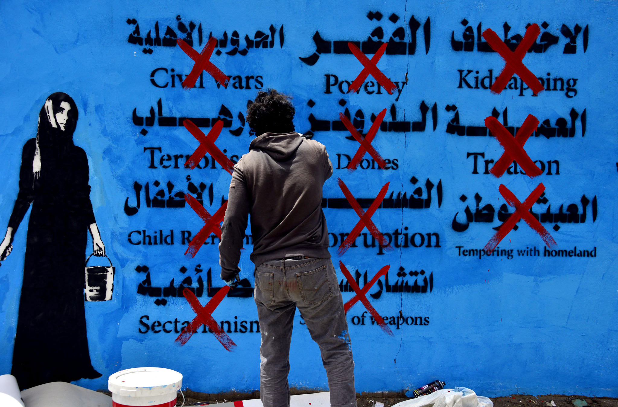 Graffiti campaign highlights concerns experienced by Yemenis...epaselect epa04282103 A Yemeni artist paints on a wall during a graffiti campaign expressing views on several social and political conflicts in Sanaía, Yemen, 25 June 2014. In response to social and political conflicts in Yemen right now, Yemeni artists and activists organized a graffiti campaign highlighting a set of concerns experienced by Yemenis, including civil wars, terrorism, child recruitment, sectarian wars, poverty, US drone war, corruption, spread of weapons and kidnapping.  EPA/YAHYA ARHAB