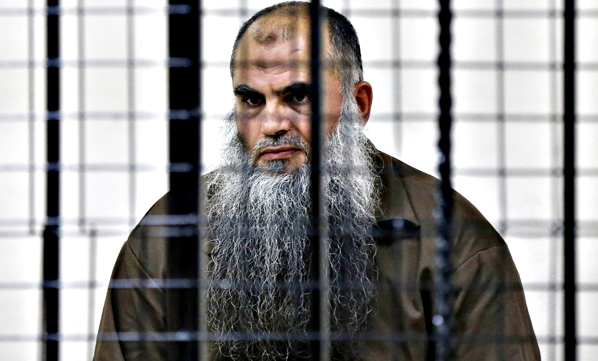 Radical Muslim cleric Abu Qatada looks on from behind bars at the State Security Court in Amman June 26, 2014. Jordan's state security court acquitted on Thursday Qatada of charges of conspiring to commit acts of terrorism, a reporter at the hearing said. The cleric, who was extradited from Britain after a lengthy legal process, will continue to be held because of separate charges related to a plot to attack tourists during Jordan's New Year celebrations in 2000.