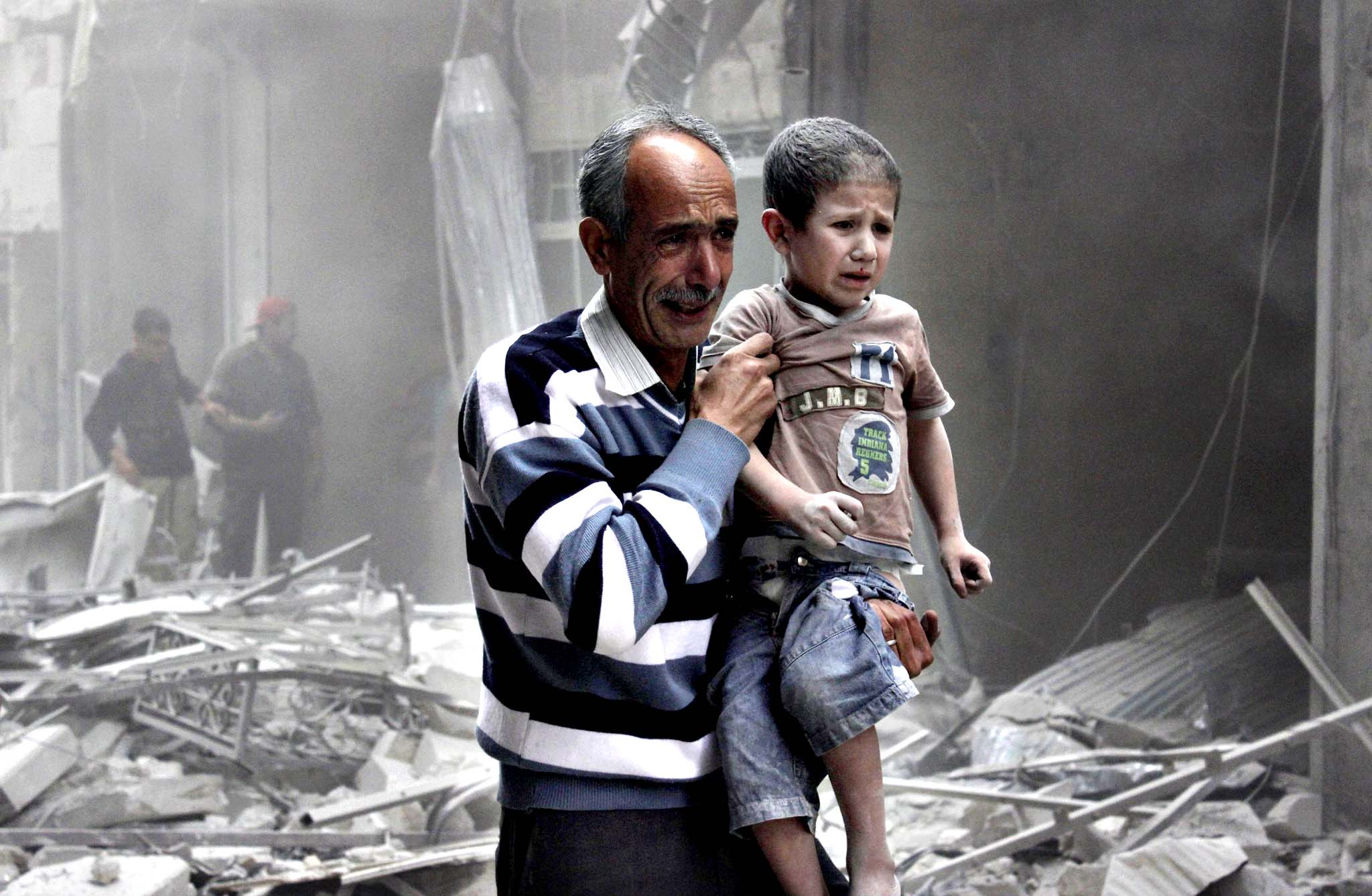 A man holds a boy who survived what activists said was an air strike by forces loyal to Syria's President Bashar al-Assad in al-Shaar neighbourhood of Aleppo June 2, 2014.