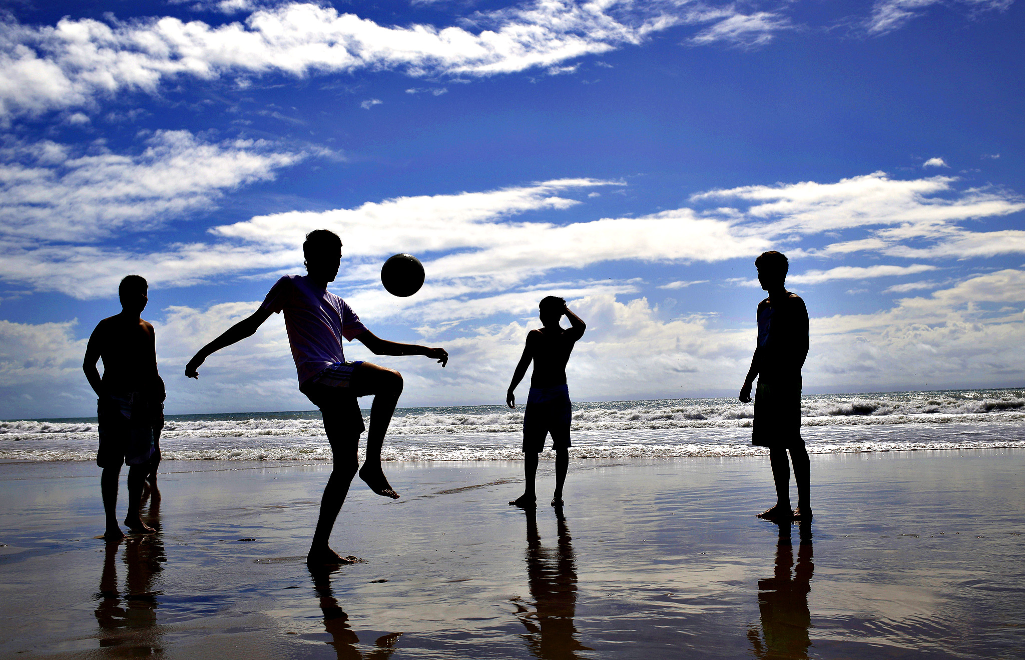 Residents and tourists play soccer on Ponta Negra beach in Natal, Brazil, Wednesday, June 25, 2014. Natal is one of many cities hosting the World Cup soccer tournament this month