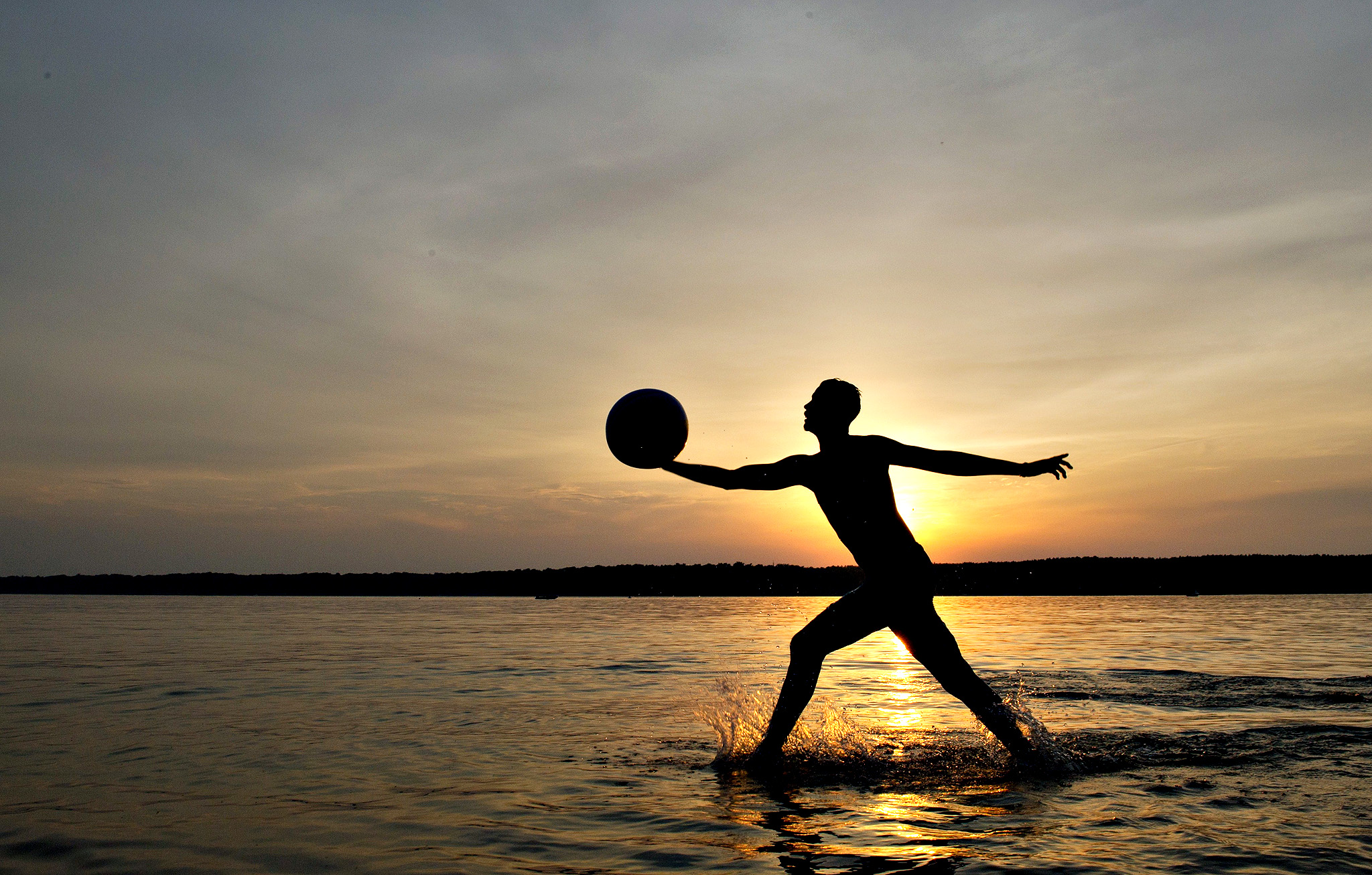 A man plays with a ball at sunset on June 10, 2014 in Berlin.