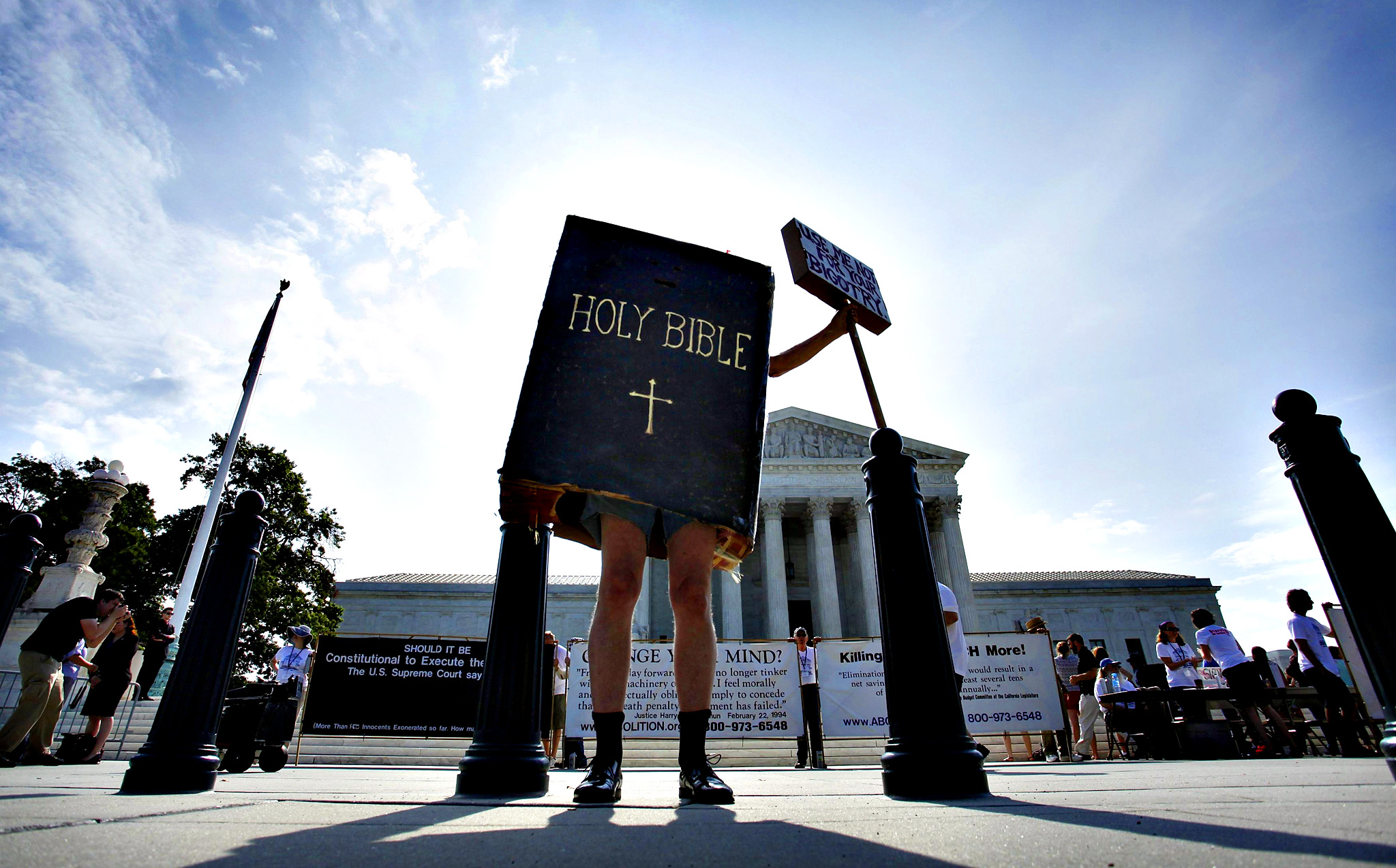 A protester dressed as a copy of the Bible joins groups demonstrating outside the U.S. Supreme Court in Washington June 30, 2014. The U.S. Supreme Court on Monday ruled that business owners can object on religious grounds to a provision of U.S. President Barack Obama's healthcare law that requires closely held companies to provide health insurance that covers birth control.