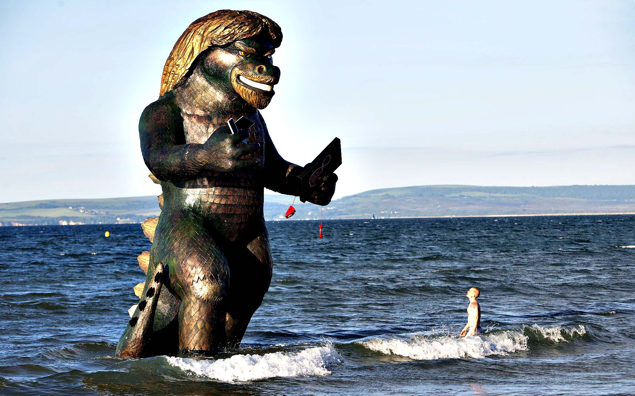 A 25 foot high sea creature resembling Richard Branson emerges from the sea on Bournemouth beach in Dorset carrying a TV, laptop, phone and mobile to celebrate the launch of Virgin Media's Big Kahuna quad-play bundle.
