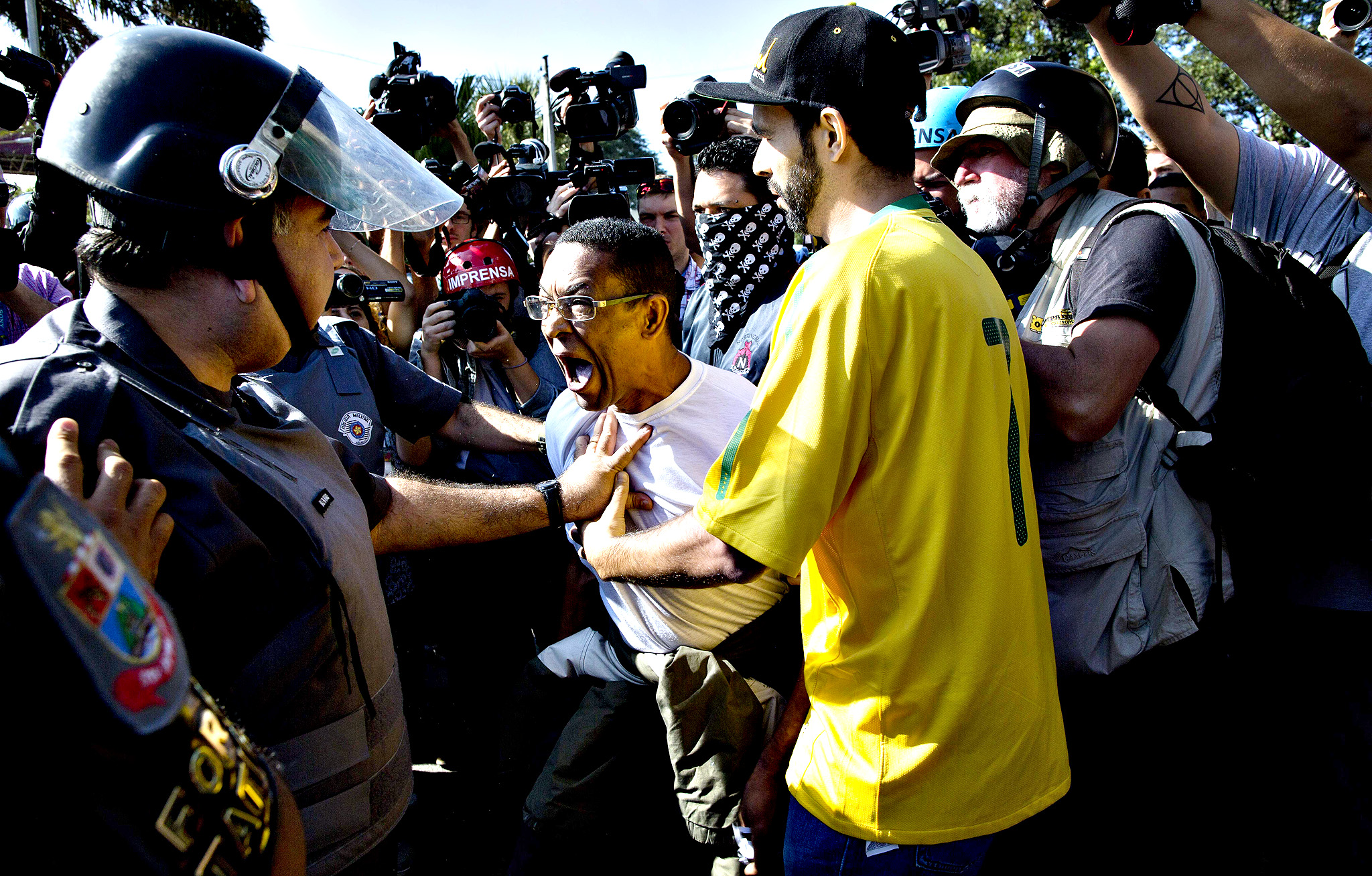 A protestor argues with police during a demonstration demanding better public services and protesting the money spent on the World Cup soccer tournament in Sao Paulo, Brazil, Thursday, June 12, 2014. Brazilian police  clashed with anti-World Cup protesters trying to block part of the main highway leading to the stadium that hosts the opening match of the tournament.