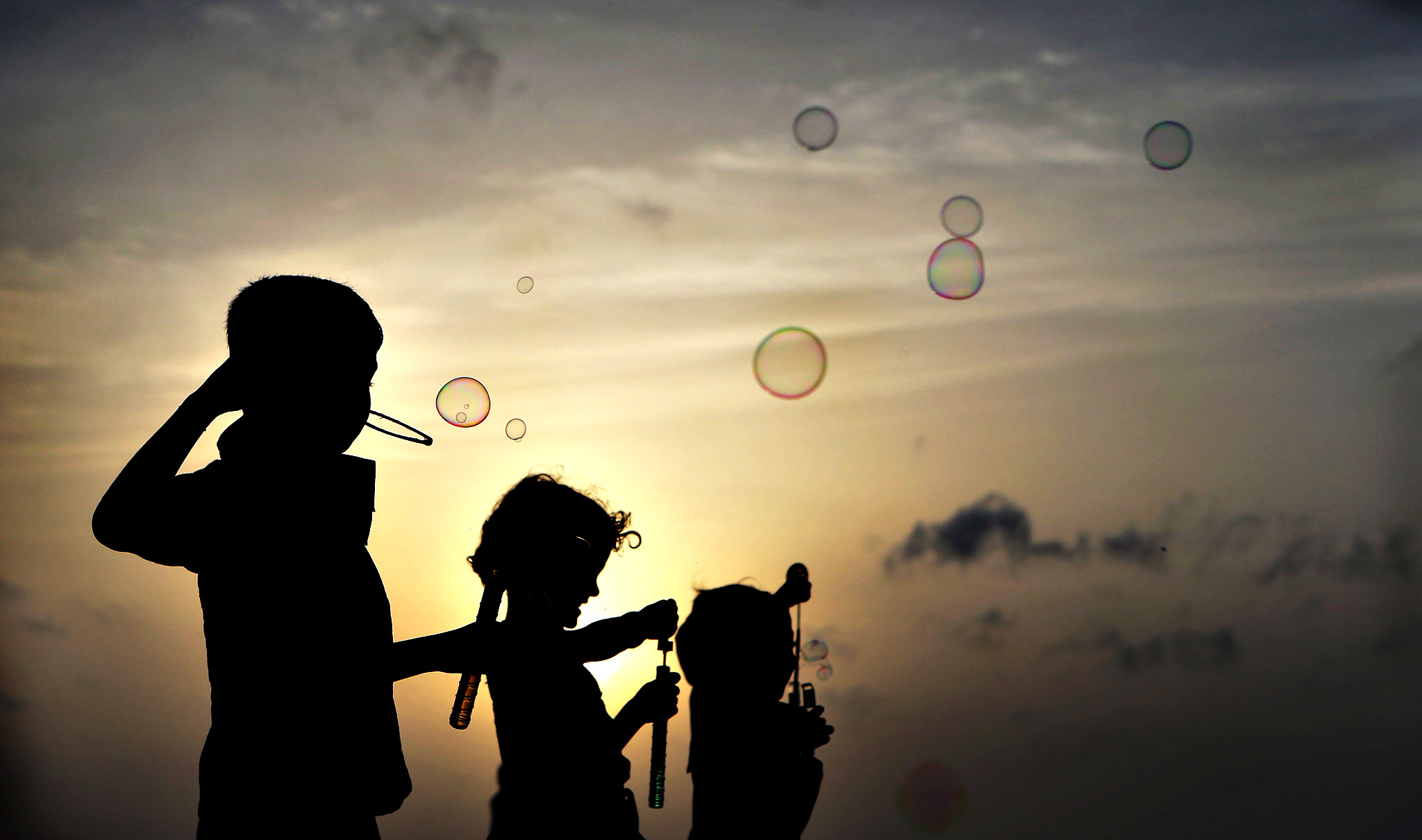 Sri Lankan children playing with soap bubbles are silhouetted against the setting Sun in Colombo, Sri Lanka, Tuesday, June 24, 2014.