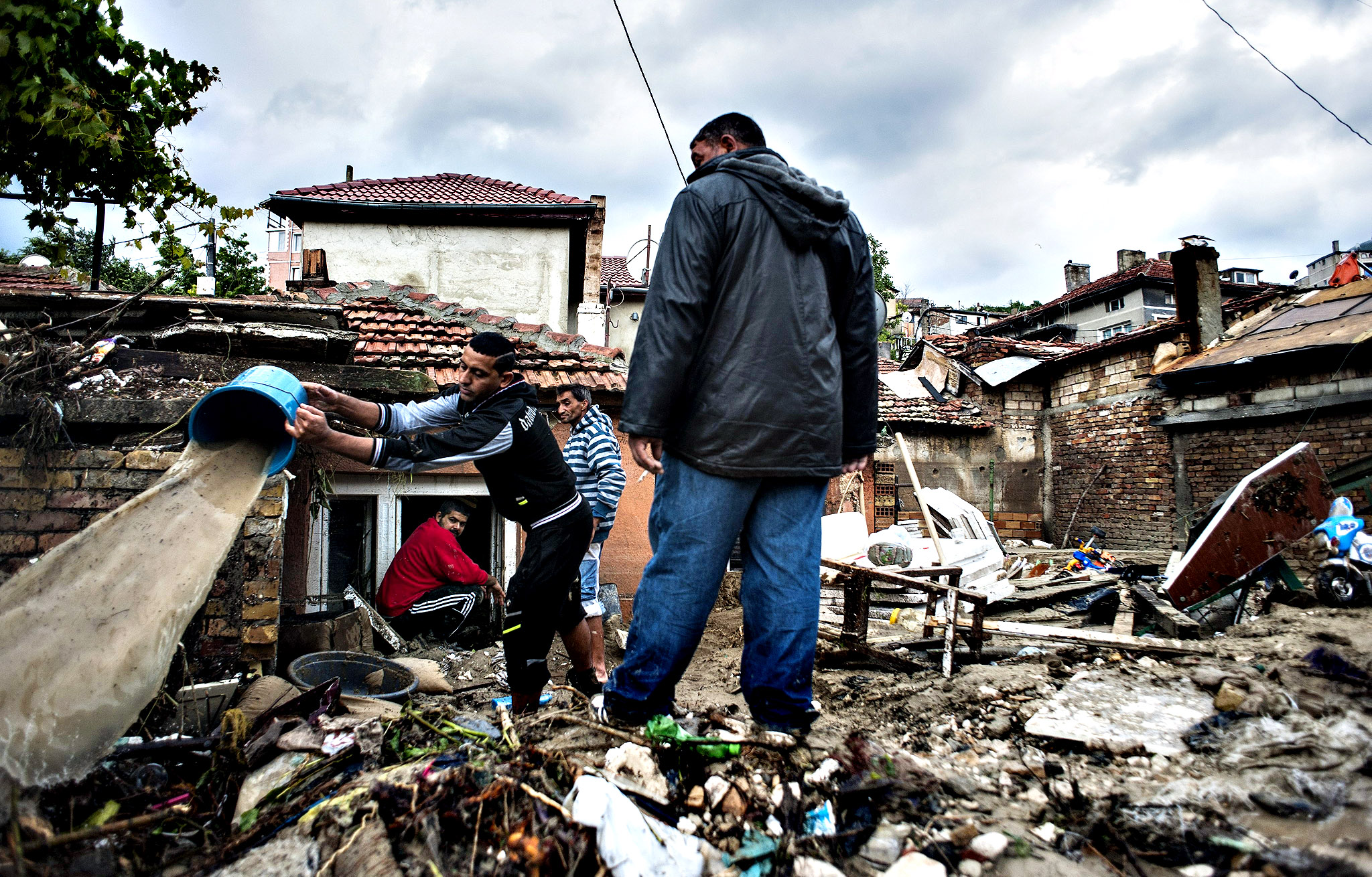 People are hand-draining their flooded house full of mud in the neighborhood of Asparuhovo in the Black Sea city of Varna, Bulgaria, 20 June 2014. At least 11 people, two of them children, have died after torrential rains caused flooding in eastern Bulgaria, the Interior Minstry said. Ten of the victims were found in the Black Sea port of Varna and another in Dobrich, 35 kilometres to the north. Several people were still missing. Lower sections of Varna were completely submerged. The floodwaters swept cars away and the work of rescue teams was hampered because of the drifting vehicles.