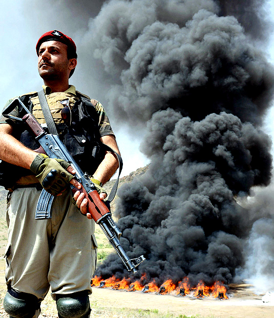 A Pakistani paramilitary soldier stands guard beside a burning pile of seized drugs during a ceremony to mark International Day against Drug Abuse and Illicit Trafficking on the outskirts of Peshawar on June 26, 2014. Pakistan's war-torn neighbour Afghanistan is the world's largest producer of opium, the raw material for heroin. Efforts to cut production have failed in the 13 years since US-led forces toppled the Taliban regime there. More than 45 percent of Afghanistan's illicit opiates pass through Pakistan on their way to markets in Europe and Asia, according to the UN Office on Drugs and Crime.