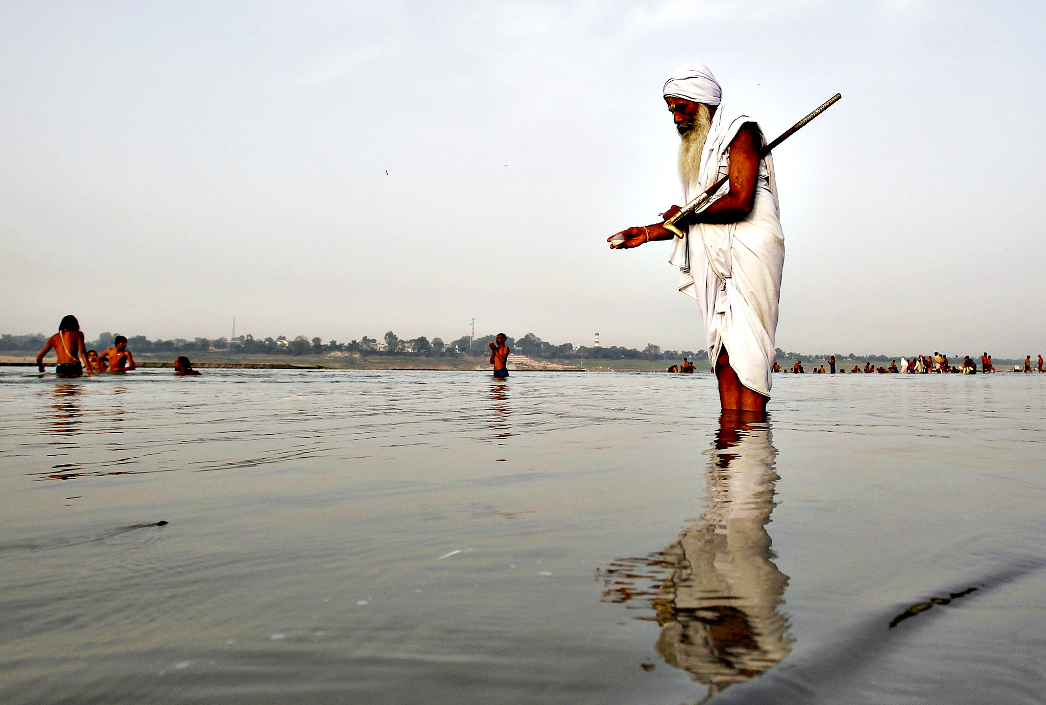 A Sadhu or a Hindu holy man offers milk to the waters of holy river Ganga as part of his morning prayers in the northern Indian city of Allahabad June 26, 2014.