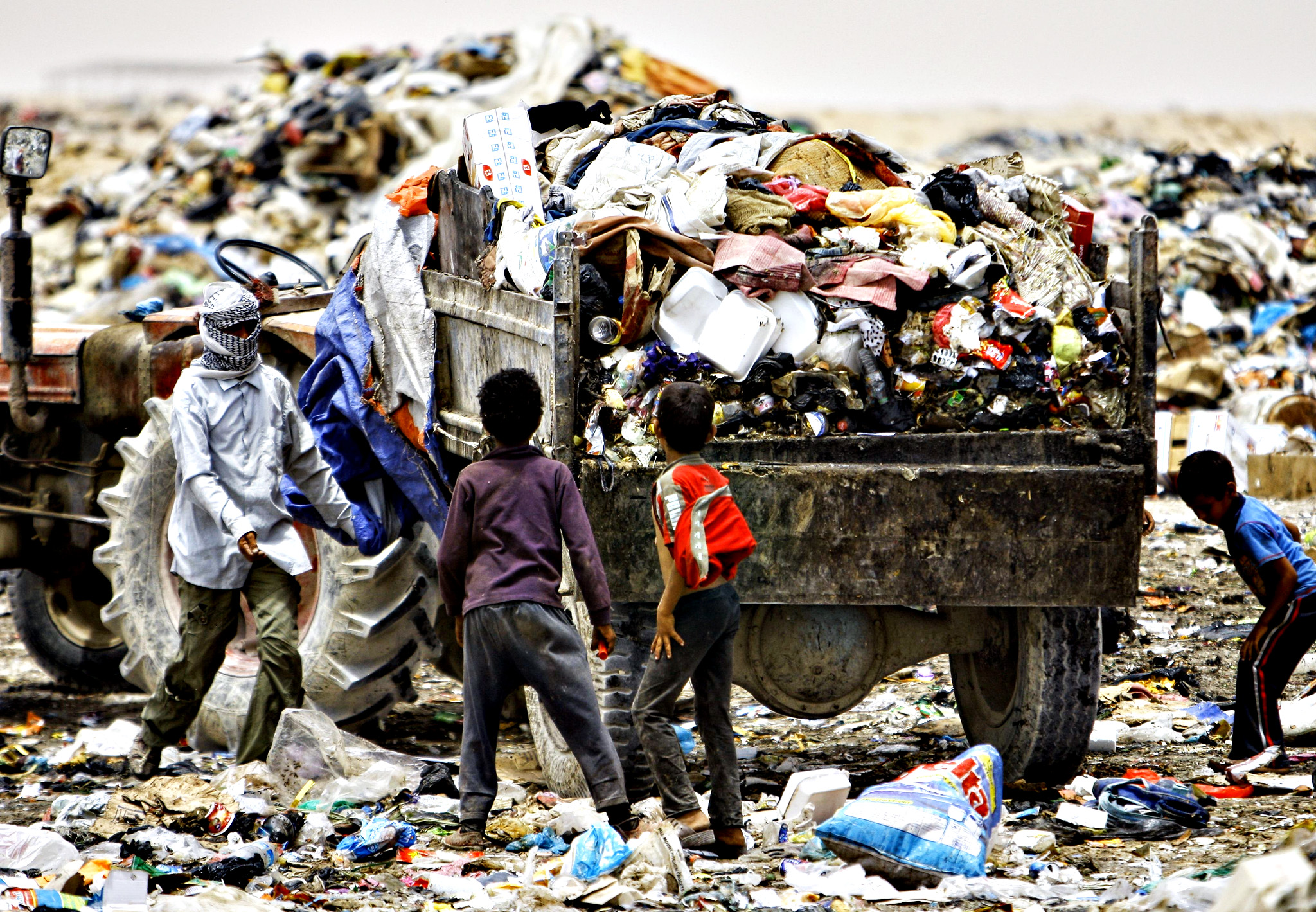 Iraqi children search through garbage for recyclable items on June 10, 2014, at a waste dump on the outskirts of the shrine city of Najaf, in central Iraq.
