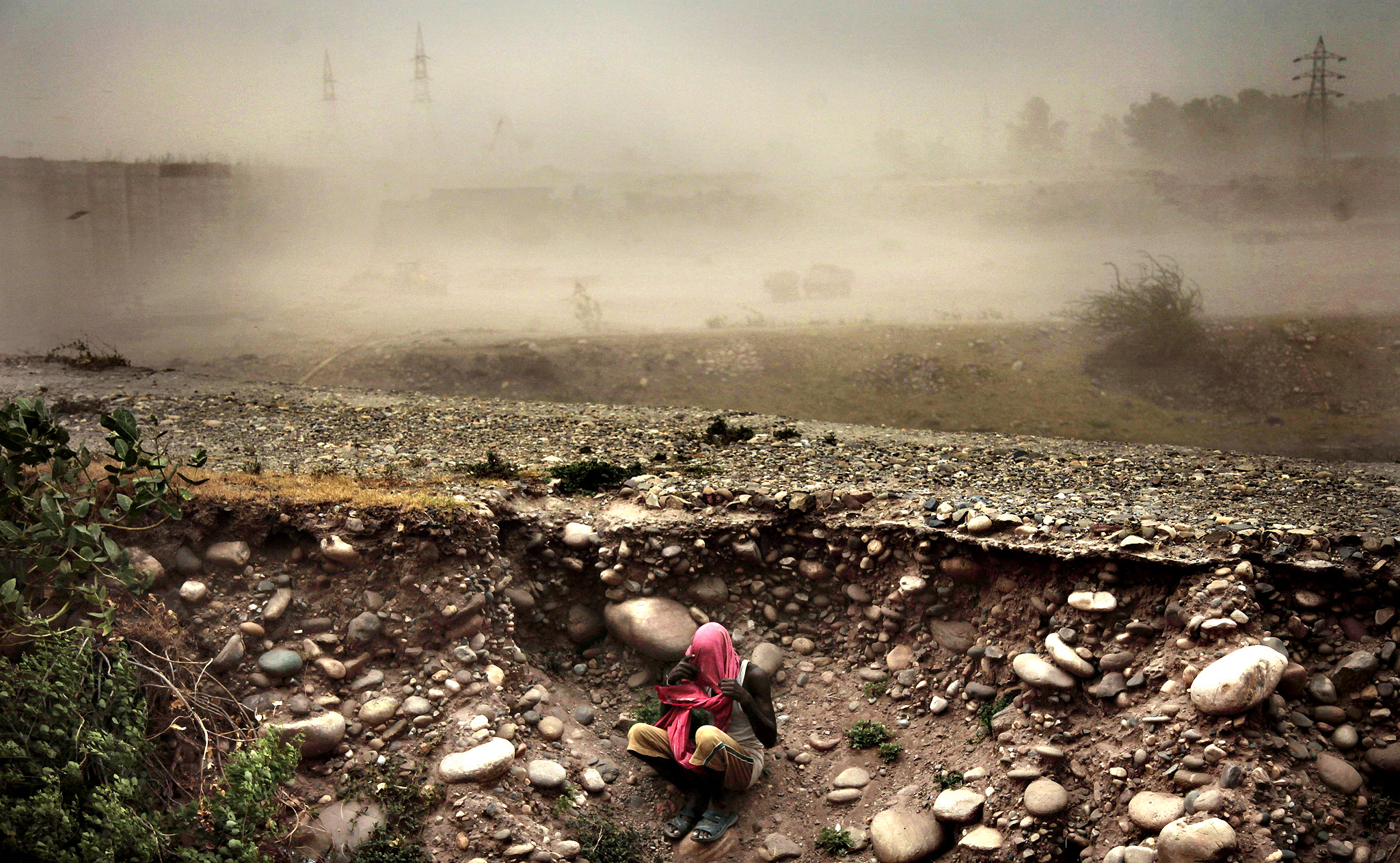 An Indian man sits beneath the road level with his face covered during a powerful dust storm in Jammu, India, Monday, June 16, 2014.