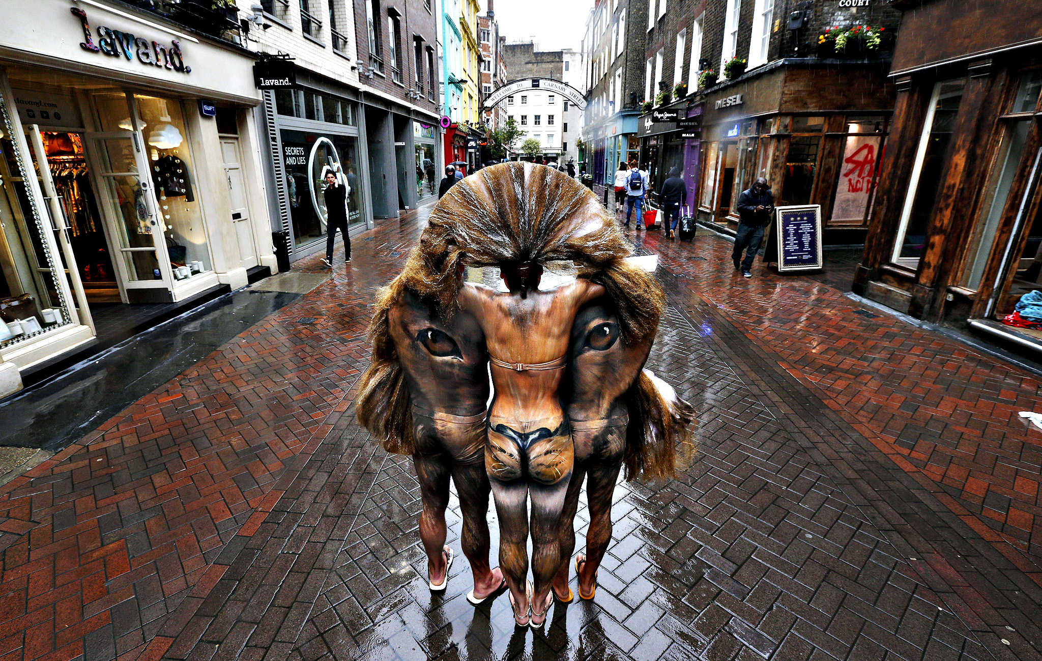 Hand-painted models depicting a lion's head, pose for the photographers during a photo-op in central London's Carnaby Street, Tuesday, June 3, 2014. It was part of events marking the opening of the Zoological Society of London(London Zoo) first ever pop-up shop on the famous street, part of the Lions400 campaign to expose the plight of the endangered Asian lion.