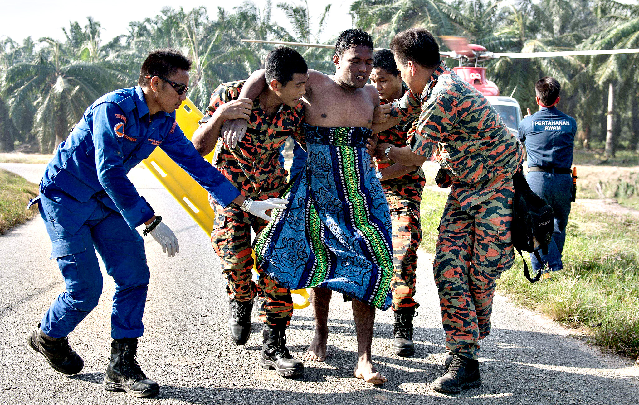 A Malaysian search and rescue team helps a rescued victim (C) from a capsized boat in Kelanang Jetty, near Banting after an apparently overloaded boat carrying Indonesian illegal migrants sank in seas off western Malaysia on June 19, 2014. The boat that sank off Malaysia with 97 Indonesian illegal migrants was likely carrying three times more passengers than it could safely transport, authorities said on June 19 as they expanded a search for 26 still missing.