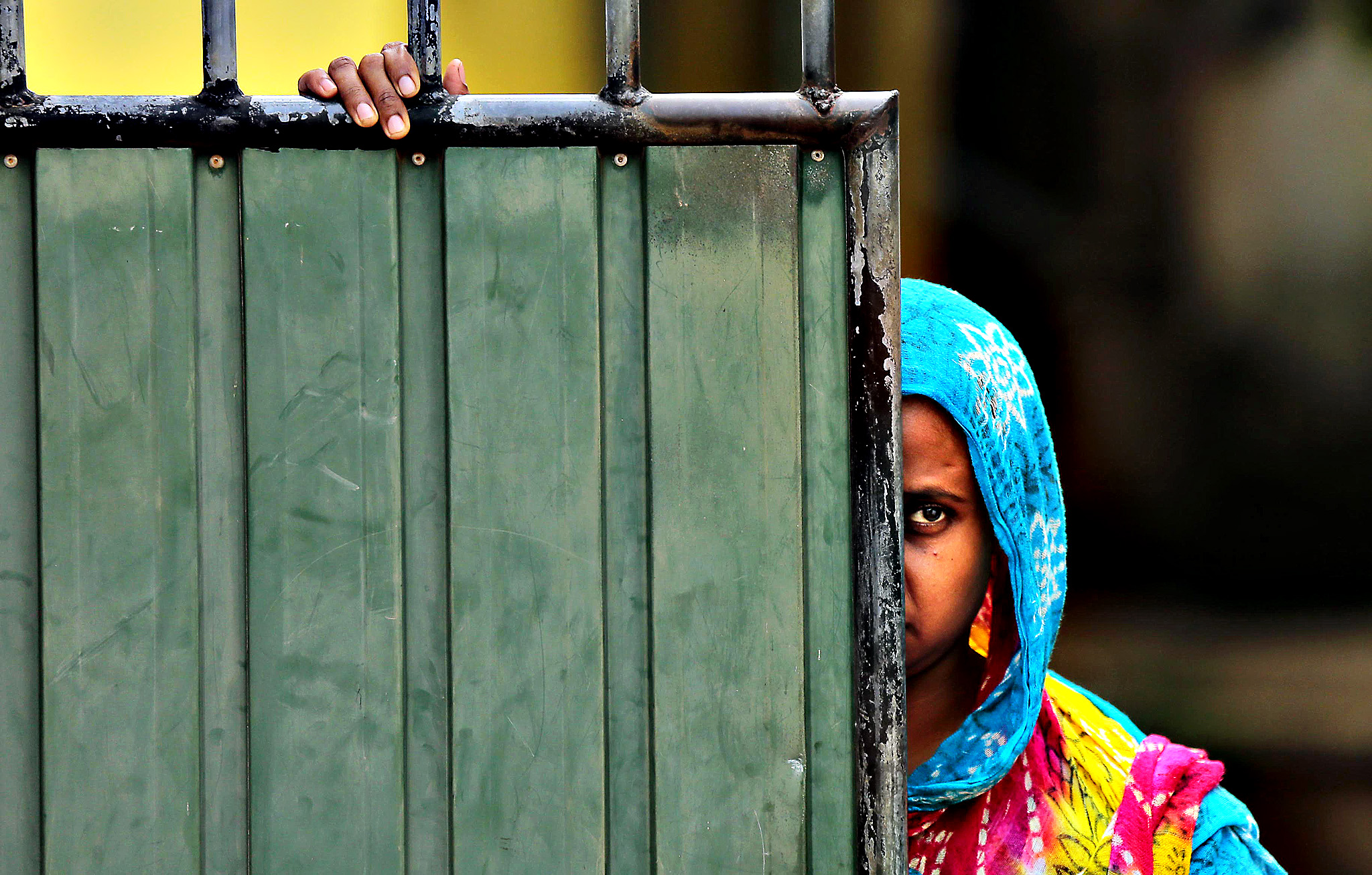 A Sri Lankan Muslim woman looks out on the street, in Aluthgama, town, 50 kilometers (31.25 miles) south of Colombo, Sri Lanka, Monday, June 16, 2014. At least three Muslims were killed after a right-wing Buddhist group with alleged state backing clashed with Muslims in southwestern Sri Lanka, a government minister said Monday. Dozens of shops were burned, homes looted and some mosques attacked in the violence Sunday night in the town of Aluthgama, local residents said.