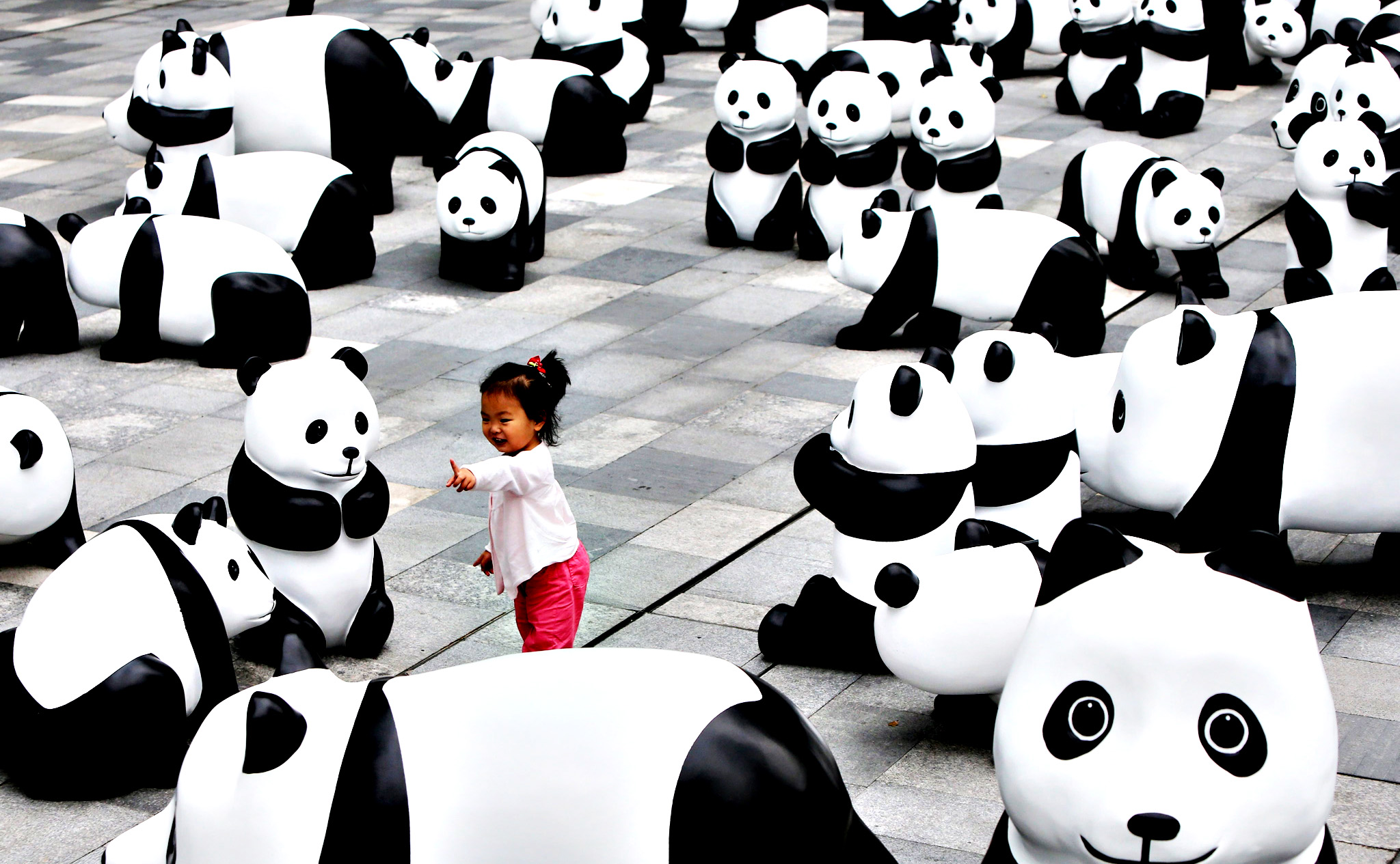 A child plays among panda sculptures at an installation in Shanghai city, China, 03 June 2014. As many as 100 panda sculptures made of recycled bamboo materials were displayed for citizens at a commercial district in a call for environmental protection.