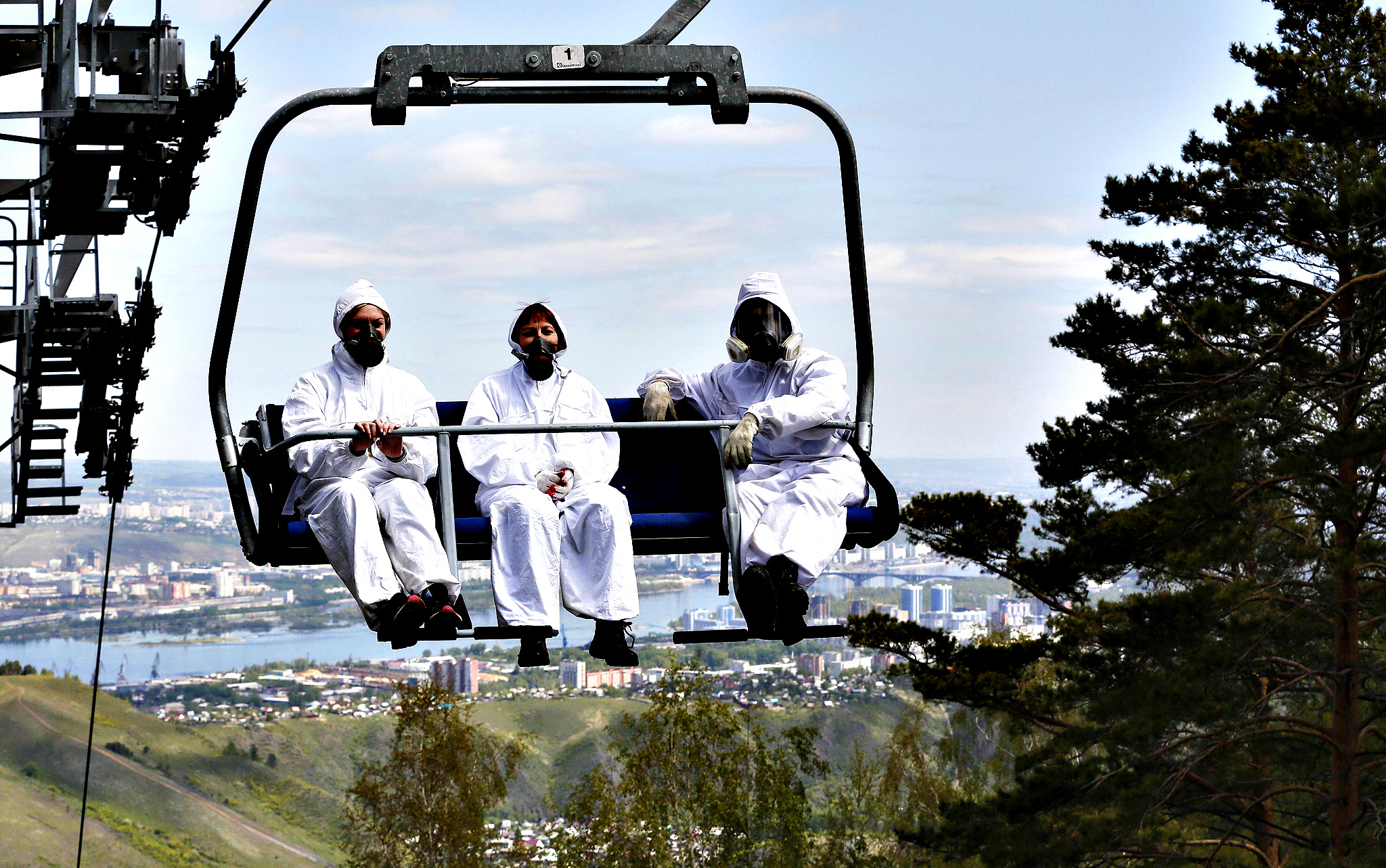 Employees of the Derate pest control company ride on a chair lift at the Bobrovy Log resort area in Taiga outside Russia's Siberian city of Krasnoyarsk...Employees of the Derate pest control company ride on a chair lift at the Bobrovy Log resort area in Taiga outside Russia's Siberian city of Krasnoyarsk, June 3, 2014.