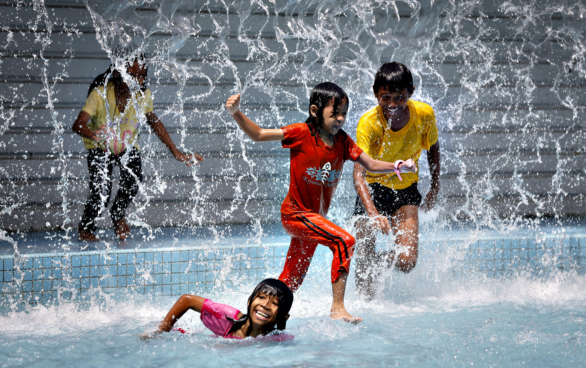 Children play in the pool in front of Malaysia's landmark Petronas Twin Towers in Kuala Lumpur, Malaysia, Thursday, June 12, 2014.