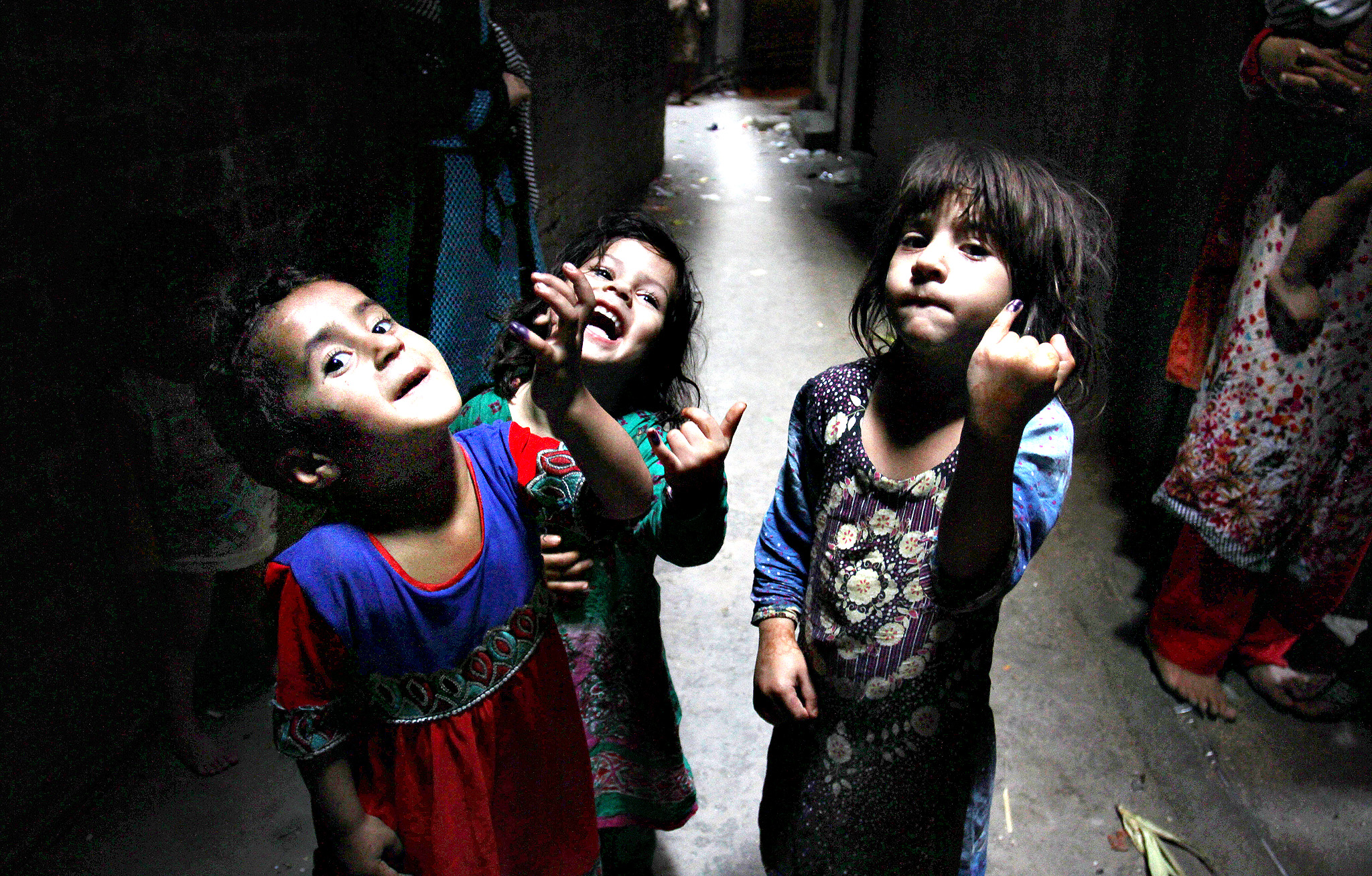 Pakistani girls show their fingers being marked after receiving polio vaccine in Lahore, Pakistan, Tuesday, June 3, 2014. Pakistan required  all travelers leaving the country to obtain a polio vaccination, the health ministry said