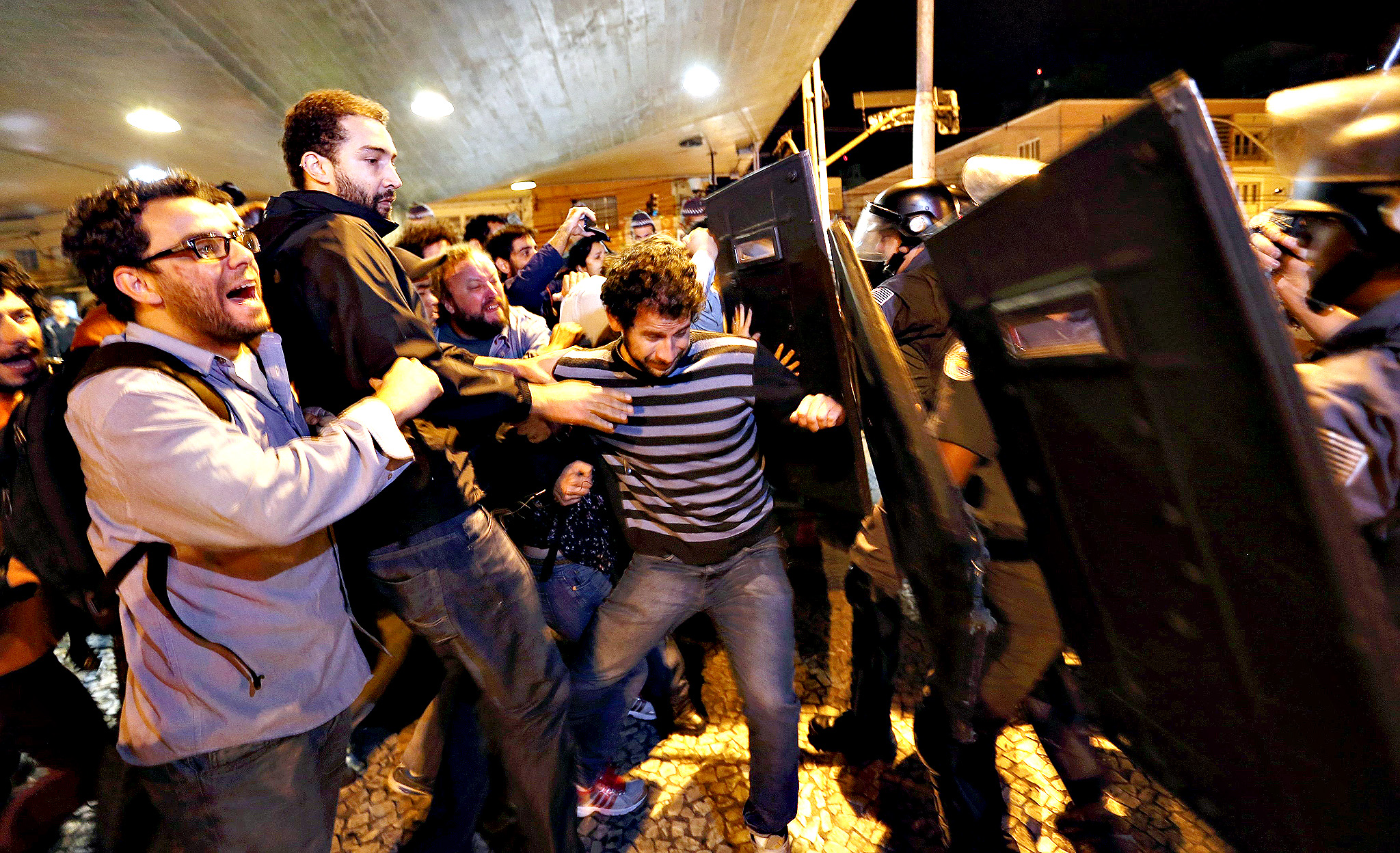 Protesters scuffle with police outside the closed entrance of Ana Rosa subway station during the fifth day of metro worker's protest in Sao Paulo June 9, 2014. A court set a 500,000 reais penalty ($223,000) for each day they stay off work from Monday and also declared the strike illegal, complicating preparations for the World Cup opening match.