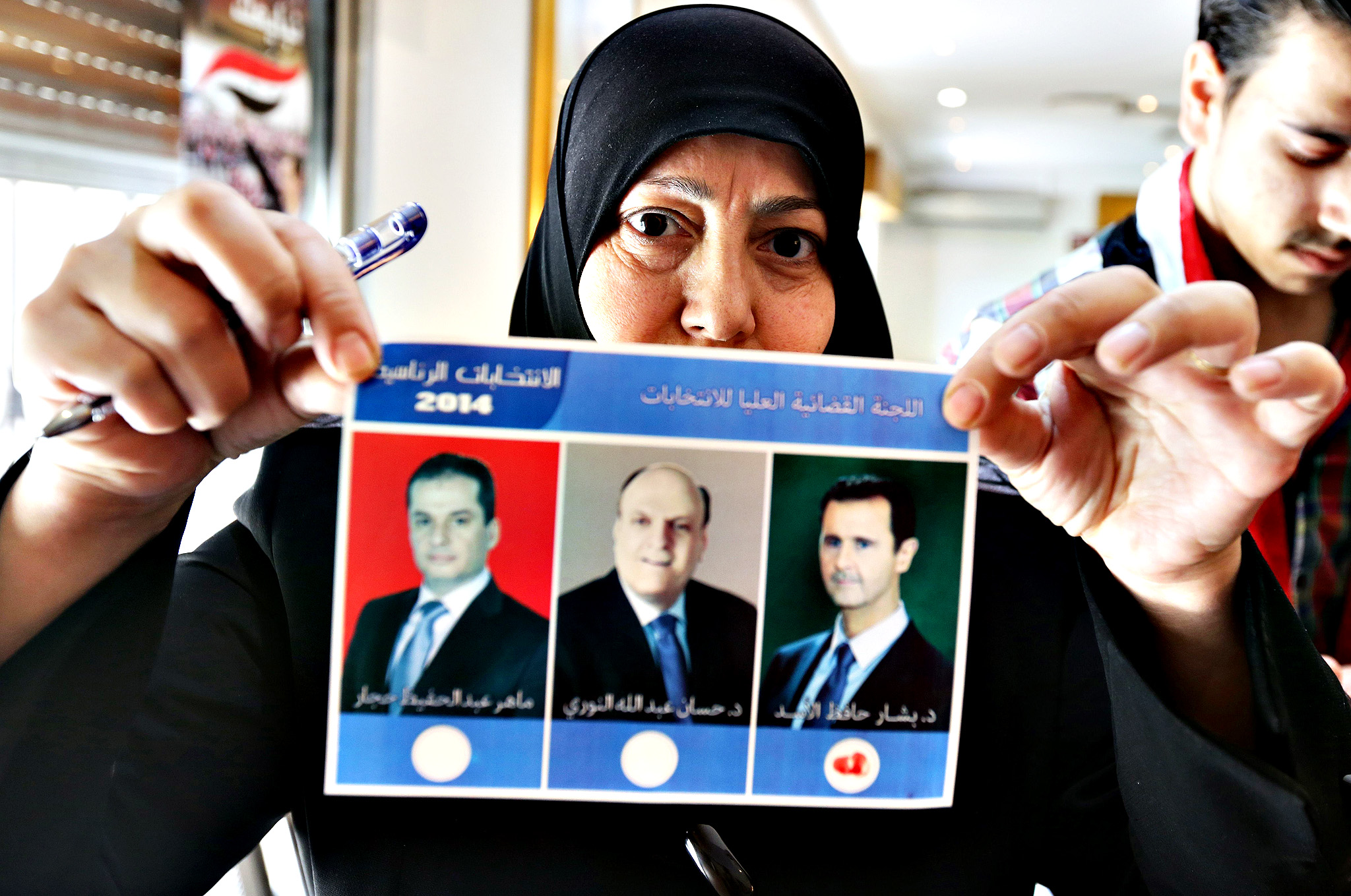"A Syrian woman shows a ballot paper bearing the portraits of the three presidential candidates (LtoR): Maher Abdel Hafiz Hajjar, Hassan Abdallah al-Nuri and President Bashar al-Assad on June 3, 2014 during the presidential election at a polling station in central Damascus. Voting offices opened in Syrian regime-held areas for a presidential election that al-Assad is certain to win, and that has been slammed as a ""farce"" by the opposition."