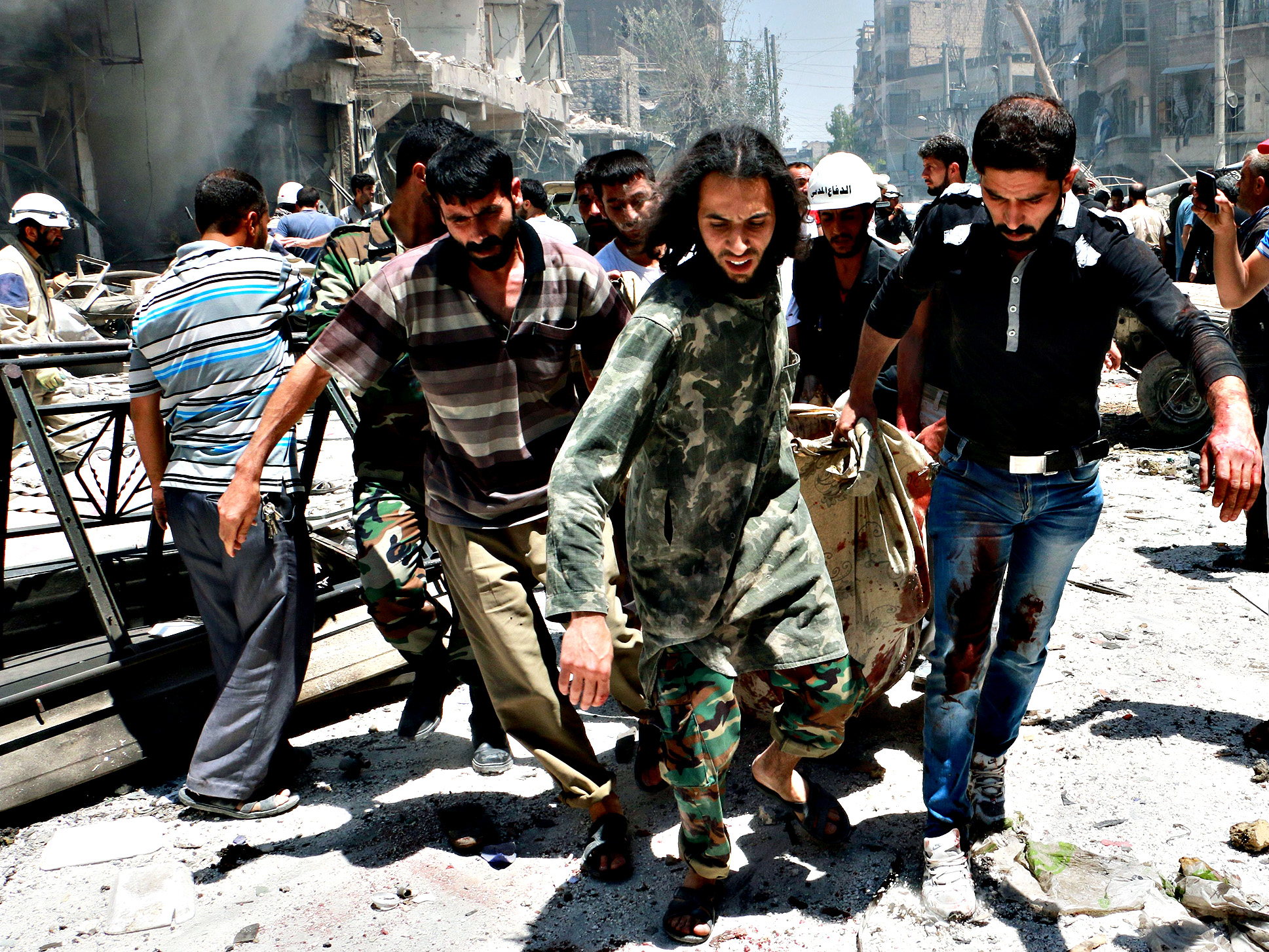 Rescuers carry a body after Syrian regime helicopters allegedly dropped barrel bombs on the Sukkari neighbourhood, an opposition-held district in the northern Syrian city of Aleppo, on June 16, 2014,  killing at least 20 people, including several children, according to the Syrian Observatory for Human Rights.