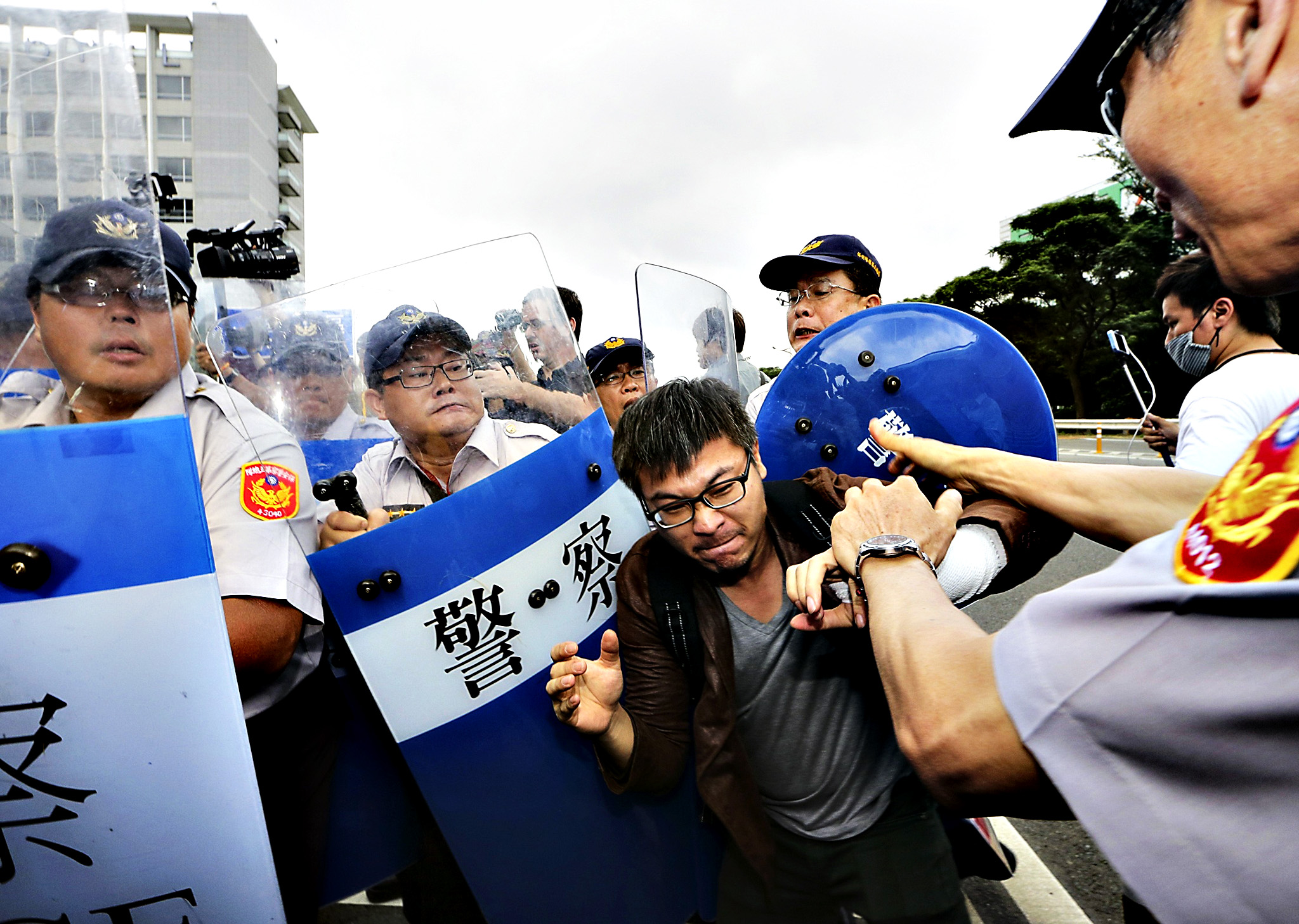 An pro-democracy activist scuffles with police officers while Zhang Zhijun, director of China's Taiwan Affairs Office meets with Taiwan's Mainland Affairs Council minister Wang Yu-chi, in Taoyuan June 25, 2014. Zhang, China's top official in charge of Taiwan ties will make a landmark visit to the island this week to try to woo Taiwanese who remain suspicious about a pending trade pact as well as meet a senior figure from the pro-independence opposition.