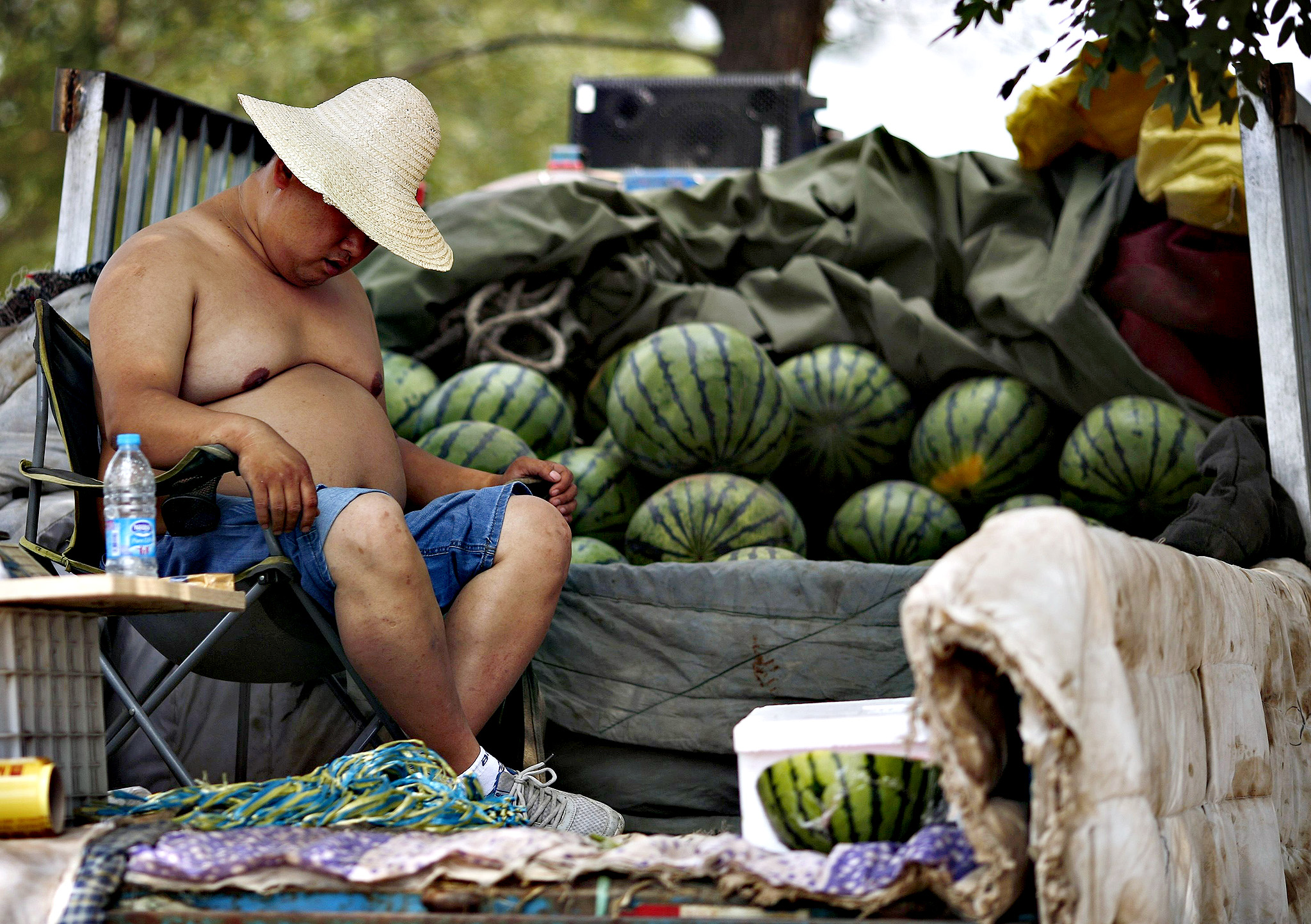 A watermelon vendor takes a nap while waiting for customers during a hot day in Beijing June 5, 2014.
