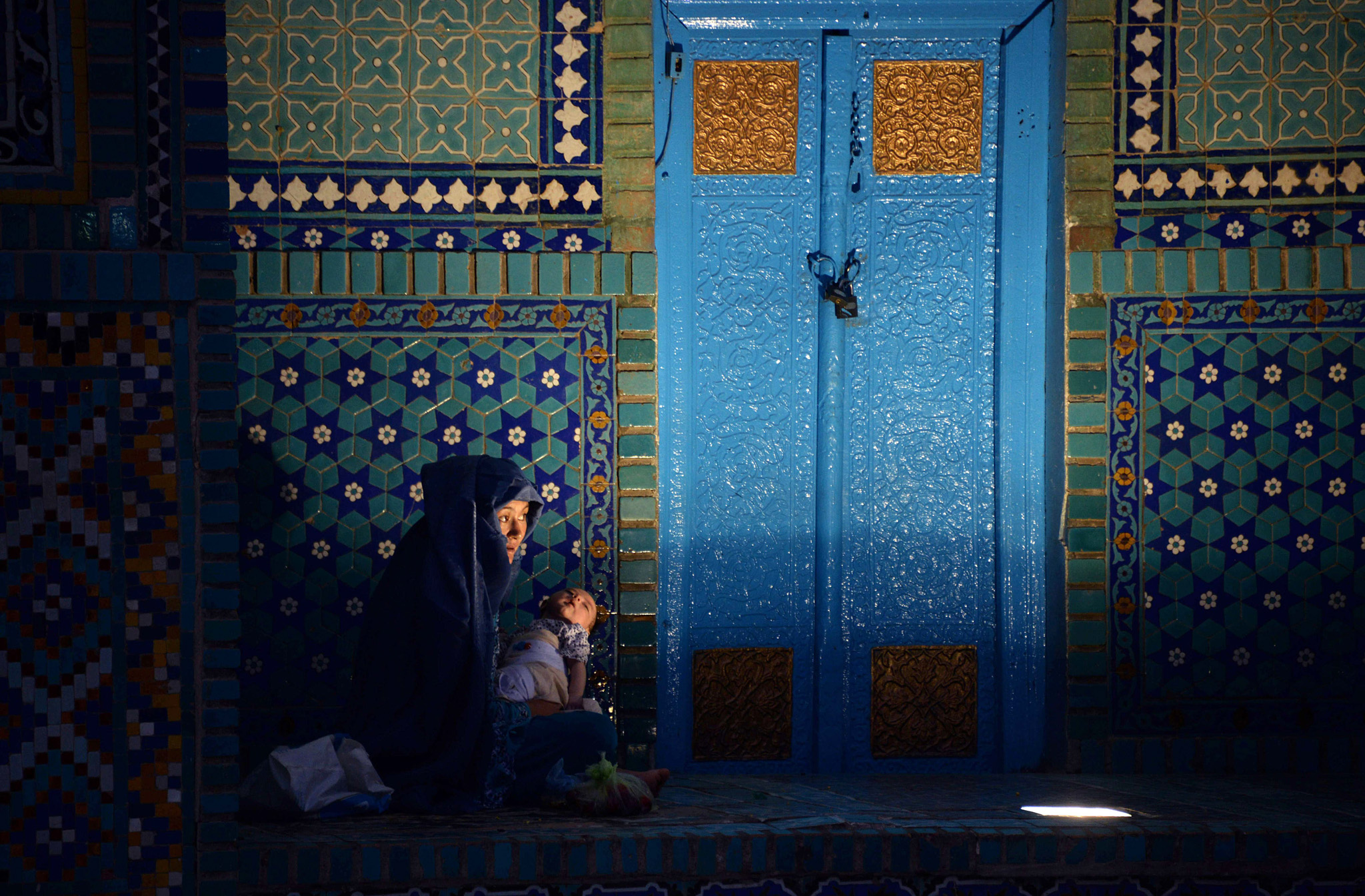 his photo taken on June 30, 2014 shows an Afghan burqa-clad woman waiting to break fast during the holy month of Ramadan at the Hazrat-e-Ali shrine, or Blue Mosque in Mazar-i-Sharif.    Across the Muslim world, the faithful fast from dawn to dusk, and abstain from eating, drinking, smoking and having sex during that time as they strive to be more pious and charitable.  AFP PHOTO/ Farshad UsyanFA