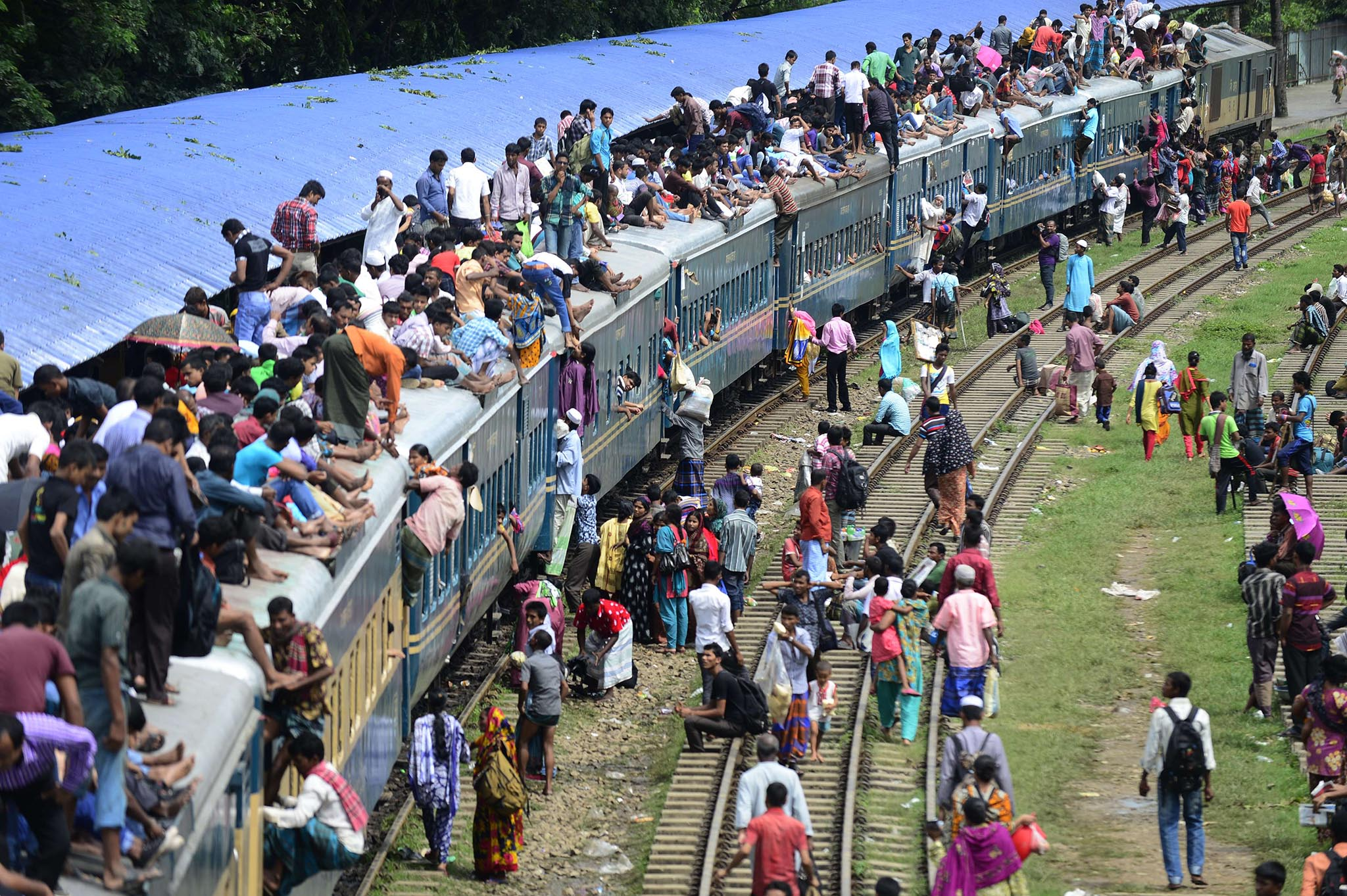 Bangladeshis wait at a train station to board packed trains