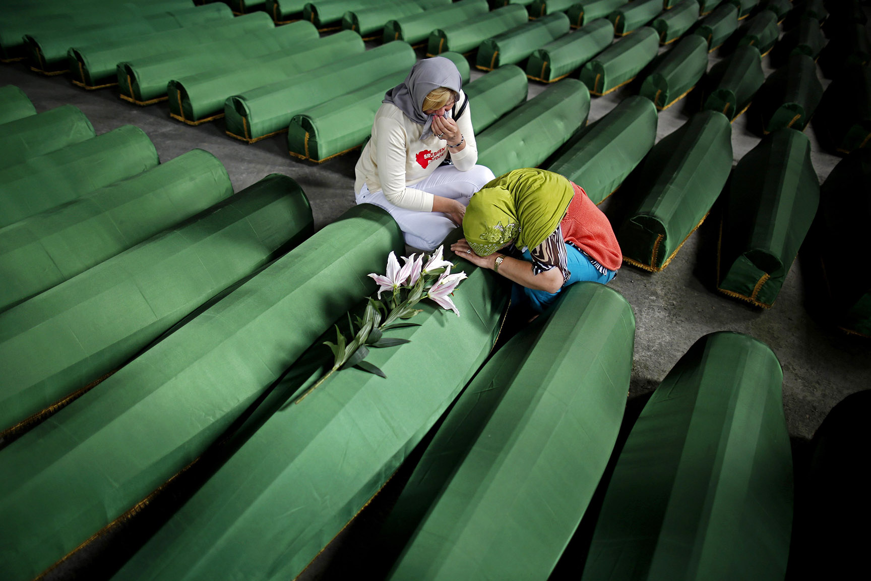 Bosnian Muslim women cry near the coffin of their relative, which is one of the 175 coffins of newly identified victims from the 1995 Srebrenica massacre, in Potocari Memorial Center, near Srebrenica