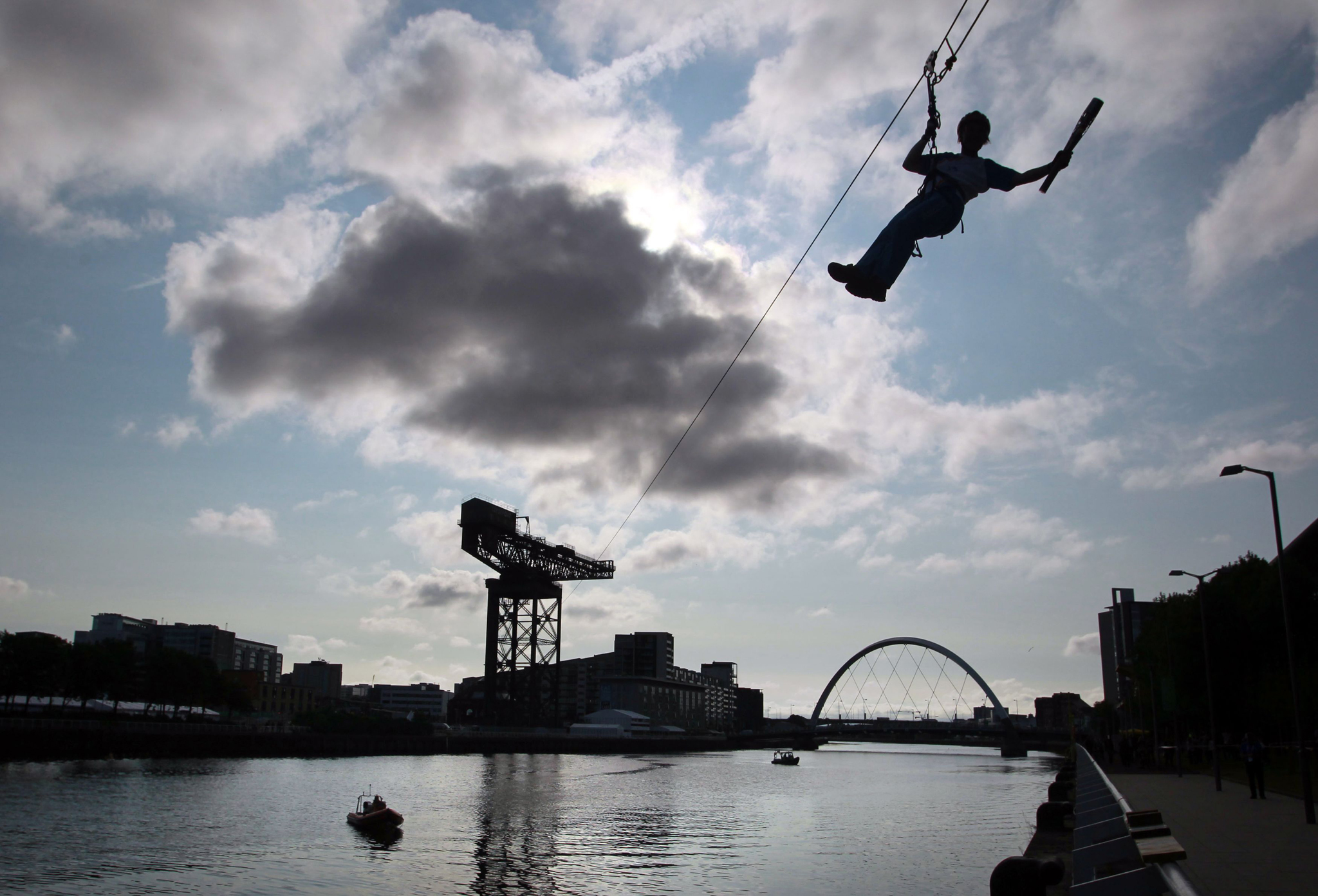 Day 38 of the Queen's Baton Relay in Scotland ...Handout photo from Glasgow 2014 Queen's Baton Relay of Batonbearer 010 Nina Saunders carrying the Glasgow 2014 Queen's Baton on a zip wire from Finnieston Crane in Glasgow. PRESS ASSOCIATION Photo. Picture date: Monday July 21, 2014. The batonbearer's name has been provided in good faith, however it has not been independently verified. Photo credit should read: David Cheskin for Glasgow 2014/PA Wire