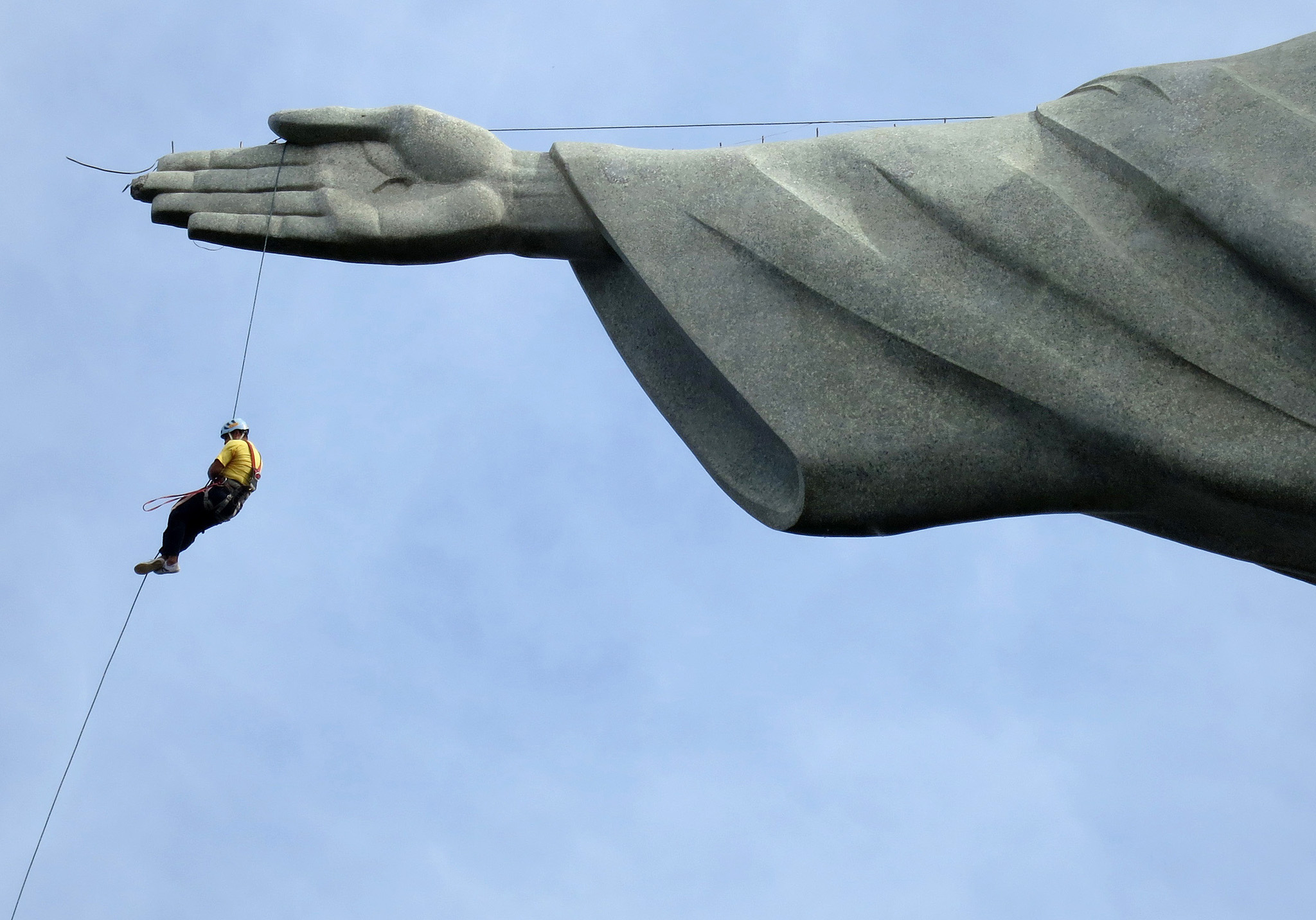 "A worker rappels from the Cristo Redentor statue at the Corcovado in Rio de Janeiro...A worker rappels from the Cristo Redentor statue at the Corcovado in Rio de Janeiro June 23, 2014. In a project called ""On The Sidelines"" Reuters photographers share pictures showing their own quirky and creative view of the 2014 World Cup in Brazil. Picture taken June 23. REUTERS/Alessandro Garofalo (BRAZIL - Tags: SPORT SOCCER WORLD CUP SOCIETY)    ATTENTION EDITORS: PICTURE 13 OF 71 FOR PACKAGE 'ON THE SIDELINES AND TO THE FINAL'  TO FIND ALL IMAGES SEARCH 'SIDELINES FINAL TOPCUP'"