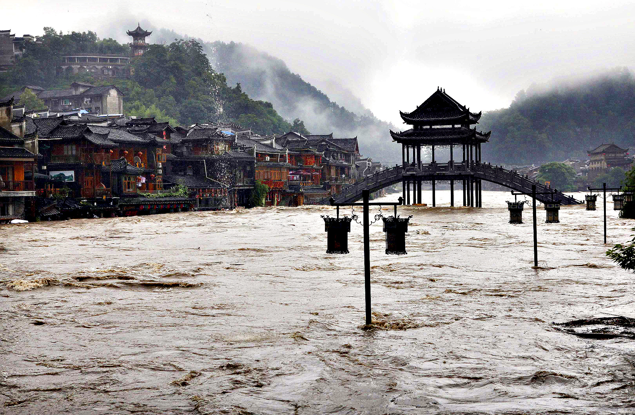 Street lamps are seen among floodwaters next to partially submerged buildings by an over flowing river at the ancient town as heavy rainfall hits Fenghuang county...Street lamps are seen among floodwaters next to partially submerged buildings by an over flowing river at the ancient town as heavy rainfall hits Fenghuang county, Hunan province July 15, 2014.  More than 50,000 locals and tourists were evacuated since Monday night as record downpours hit Fenghuang county of central China's Hunan province, Xinhua News Agency reported.
