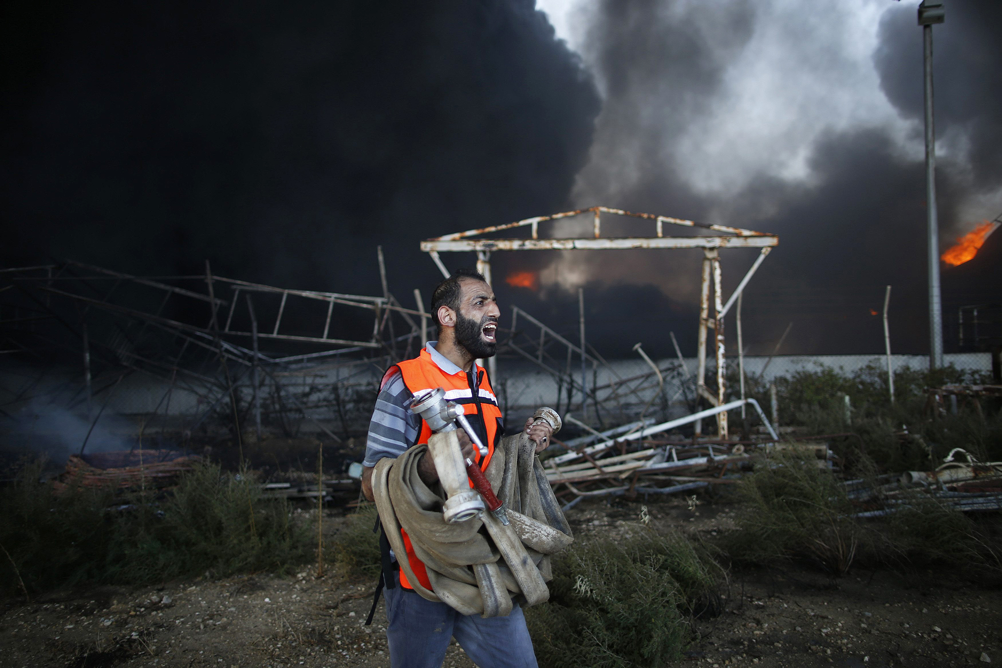 Palestinian firefighter reacts as he tries to put out a fire at Gaza's main power plant in the central Gaza Strip...A Palestinian firefighter reacts as he tries to put out a fire at Gaza's main power plant, which witnesses said was hit in Israeli shelling, in the central Gaza Strip July 29, 2014.  Israeli tank fire hit the fuel depot of the Gaza Strip's only power plant on Tuesday, witnesses said, cutting electricity to Gaza City and many other parts of the Palestinian enclave of 1.8 million people.An Israeli military spokeswoman had no immediate comment and said she was checking the report. Israel launched its Gaza offensive on July 8, saying its aim was to halt rocket attacks by Hamas and its allies. REUTERS/Mohammed Salem (GAZA - Tags: POLITICS CIVIL UNREST ENERGY TPX IMAGES OF THE DAY)