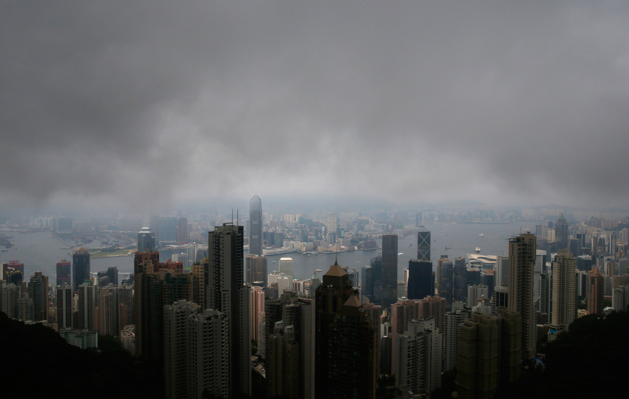 Rain clouds hang over Central in Hong Kong, Thursday, July 24, 2014. As activists vow to shut down Hong Kongís financial district in protest at Chinaís attempt to hobble democratic elections in the city, businessman Bernard Chan is preparing for the worst. Chanís investment company has added backup phone lines, bought extra laptops and stockpiled instant noodles in case its headquarters downtown is caught in the middle of the protest. (AP Photo/Kin Cheung)