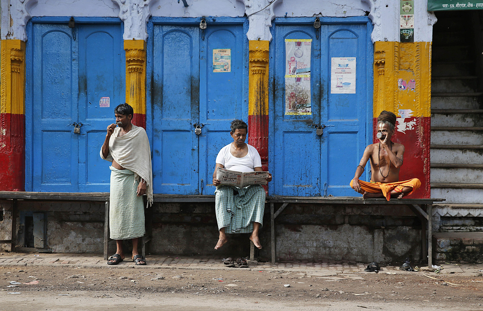 A man brushes his teeth as another reads a newspaper while a Hindu holy man sips tea in the morning in front of a closed shop in Allahabad, India, Wednesday, July 30, 2014. (AP Photo/ Rajesh Kumar Singh)